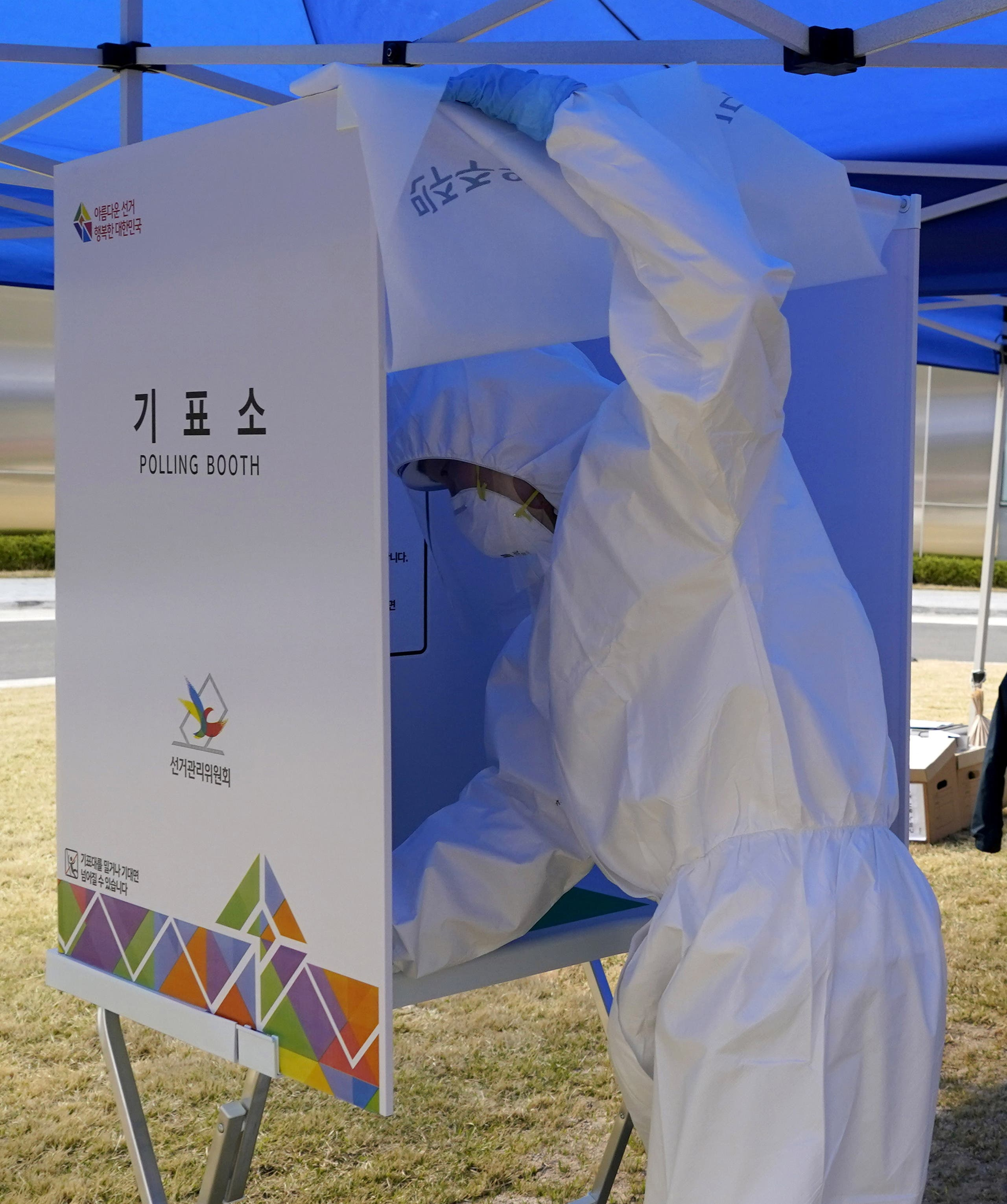 An election officer in protective gear disinfects a polling booth before South Korean patients affected with the coronavirus disease (COVID-19) arrive to cast their ballots for the parliamentary election at a polling station set up at a quarantine center in Yongin, South Korea, April 11, 2020.