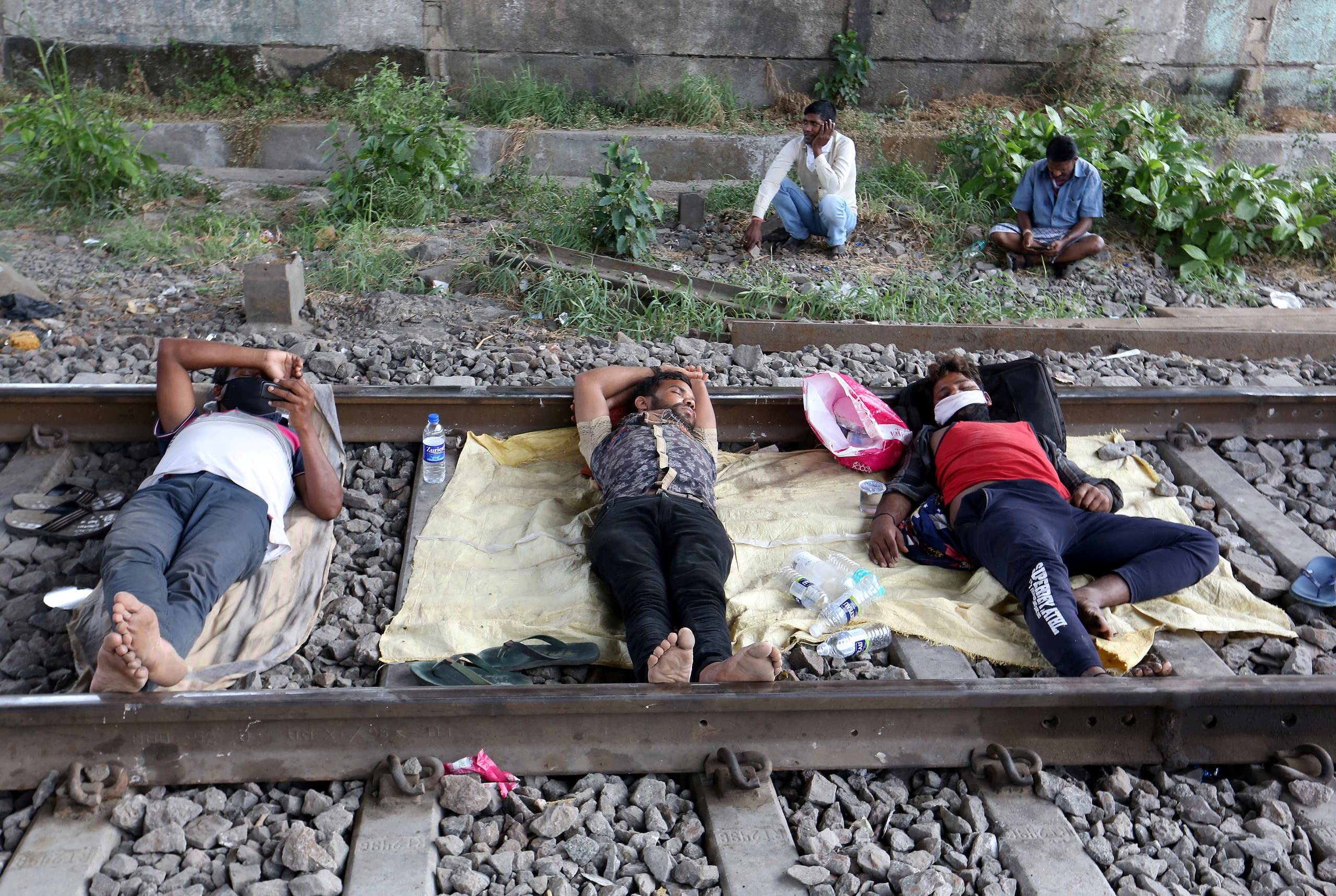 Migrant workers rest on a railway track during a 21-day nationwide lockdown to slow the spreading of coronavirus disease (COVID-19) in in Mumbai, India, on April 2, 2020. (Reuters)
