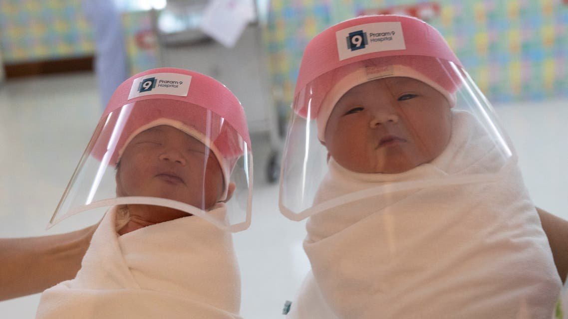 Nurses hold newborn babies wearing protective face shields at the Praram 9 hospital in Bangkok. (Reuters)