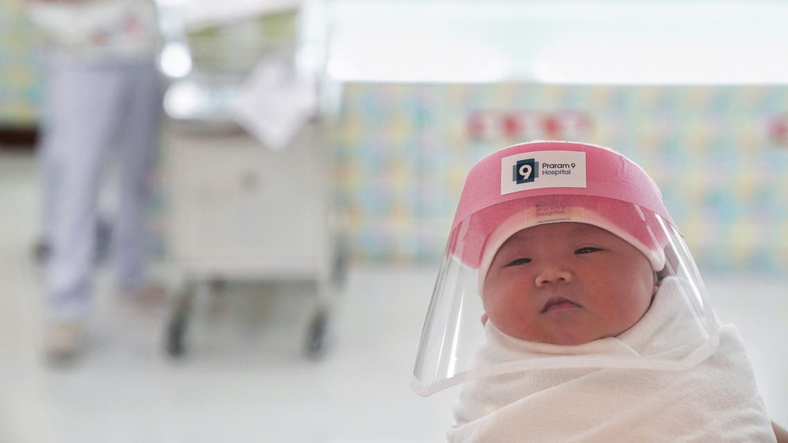 A newborn baby is seen wearing a protective face shield at the Praram 9 hospital in Bangkok. (Reuters)
