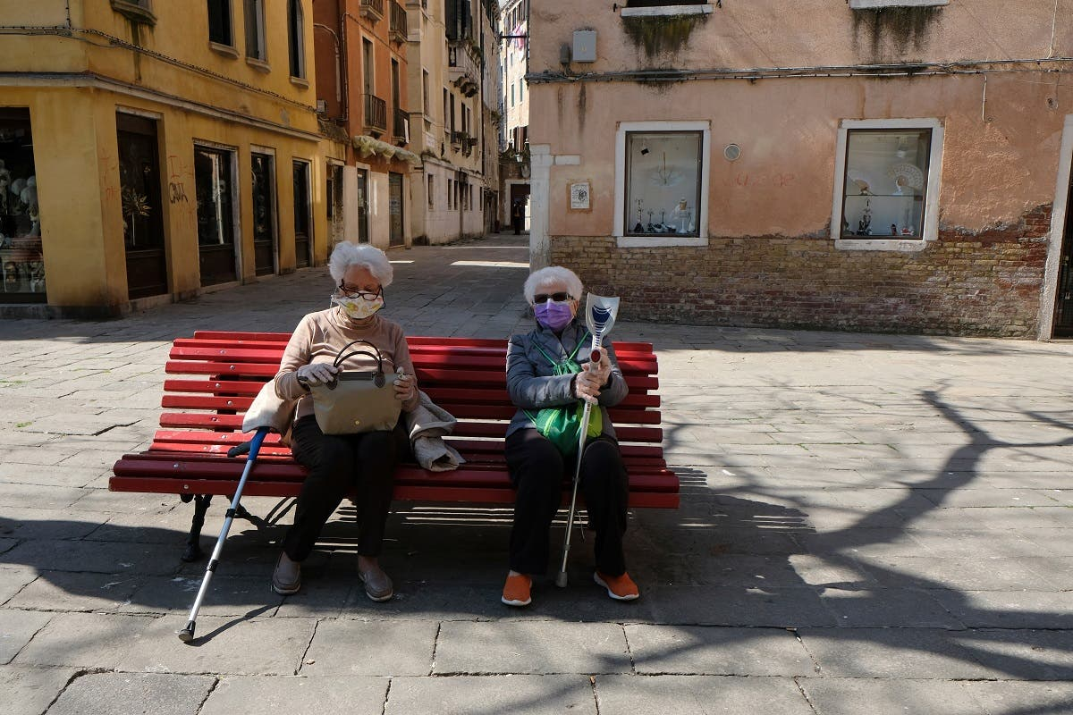 Two women with masks sit on a bench on Good Friday as Italy celebrates Easter under lockdown to try and stop the spread of the coronavirus disease in Venice, April 10, 2020. (Reuters)