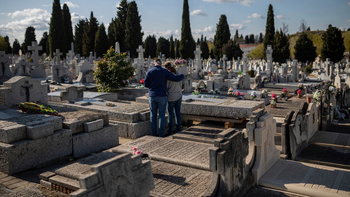 Two people attend a burial of a relative at a Madrid cemetery during the coronavirus outbreak in Madrid, Spain. (AP)