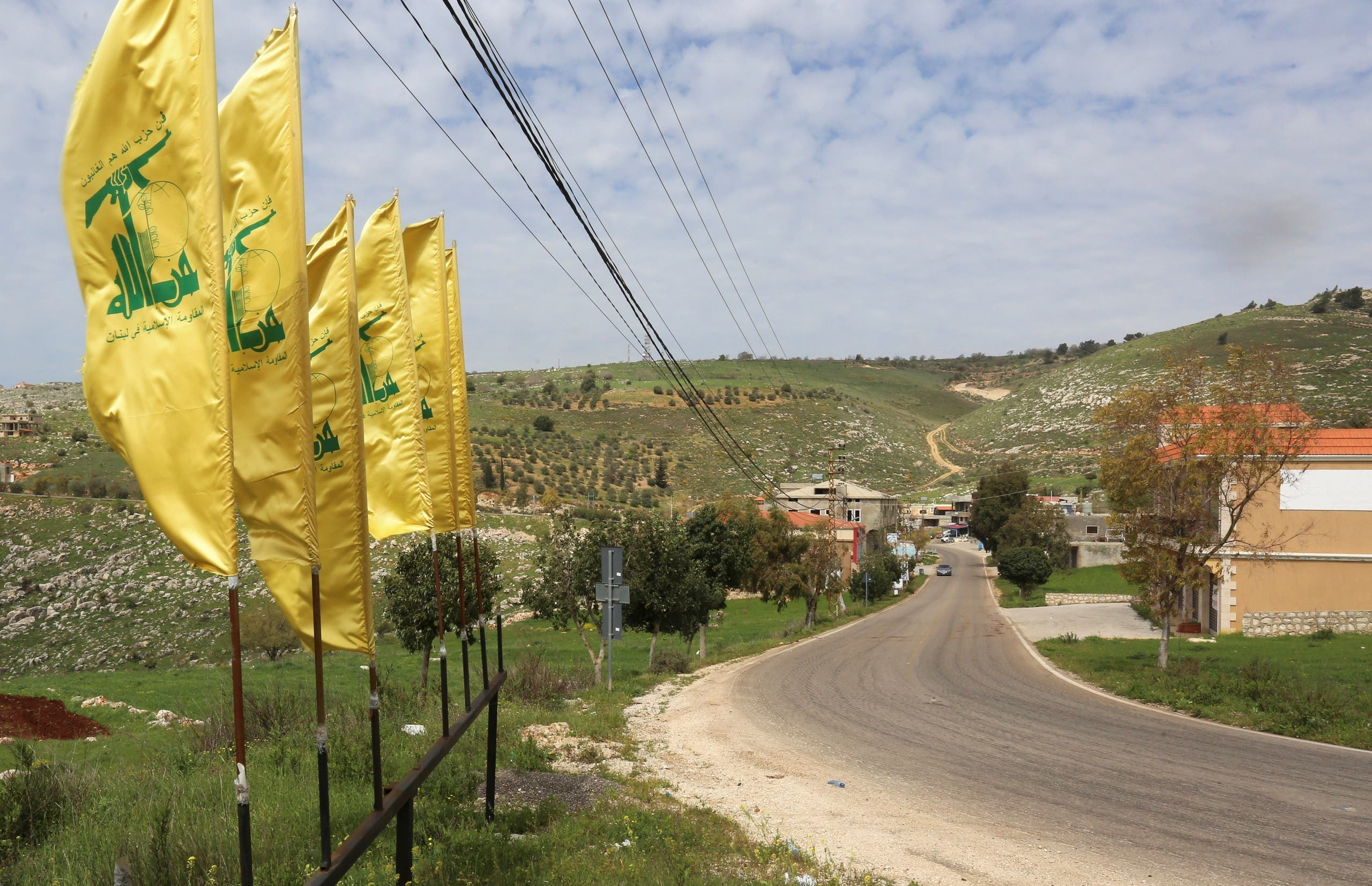 Hezbollah flags flutter along an empty street, at the entrance of Mays Al-Jabal village in Lebanon. (Reuters)
