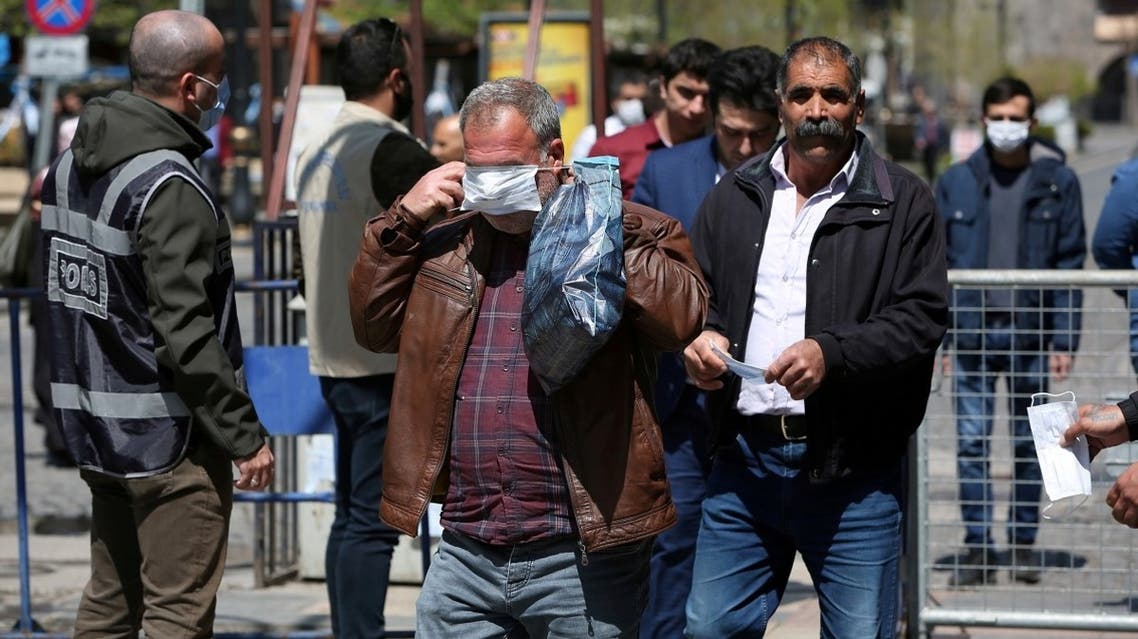 People receive free masks from a municipal worker as the spread of coronavirus disease (COVID-19) continues, in Diyarbakir. (Reuters)