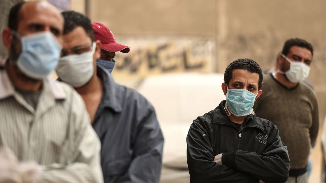 Egyptian men wearing masks wait outside a centre of non-governmental organisation Egyptian Food Bank to receive cartons with foodstuffs on April 05, 2020, as the charity distributes aid to people who lost their jobs due to the coronavirus pandemic crisis, in the Egyptian capital Cairo.