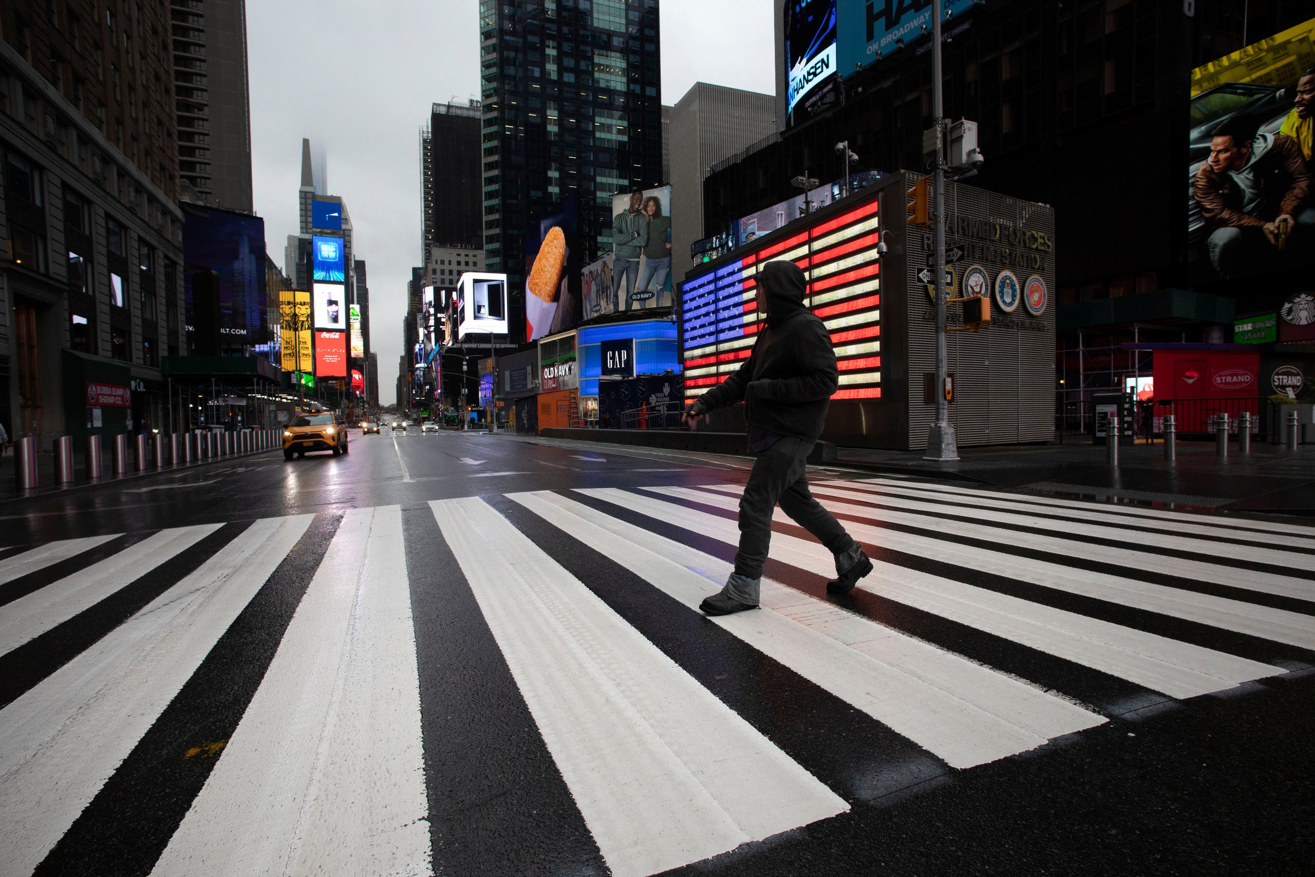 A man crosses the street in a nearly empty Times Square, which is usually very crowded on a weekday morning, Monday, March 23, 2020 in New York. (AP)