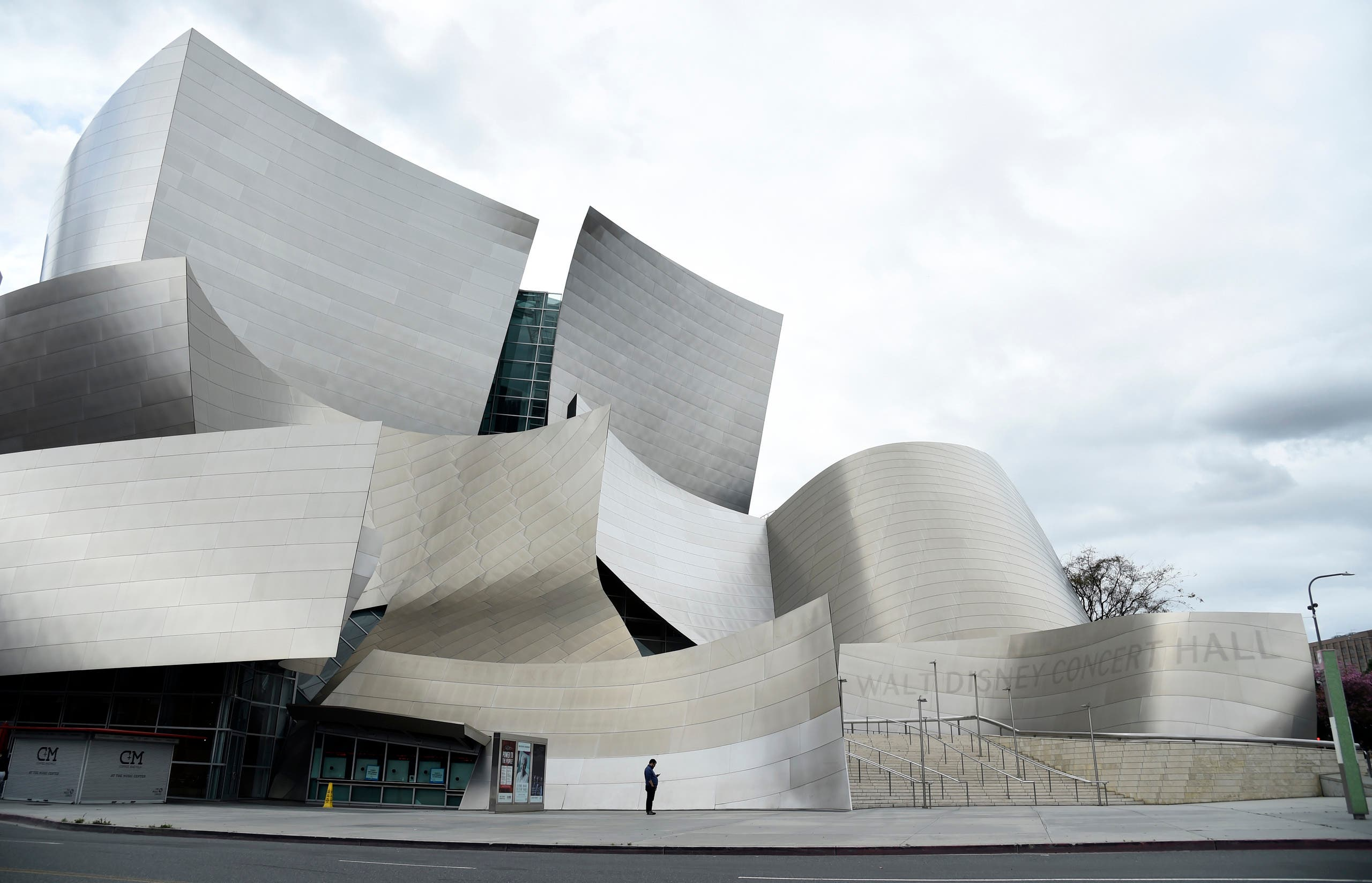 A man reads his phone on deserted Grand Avenue in front of the Walt Disney Concert Hall as stay-at-home orders continue in California due to the coronavirus, on April 10, 2020, in Los Angeles. (AP)