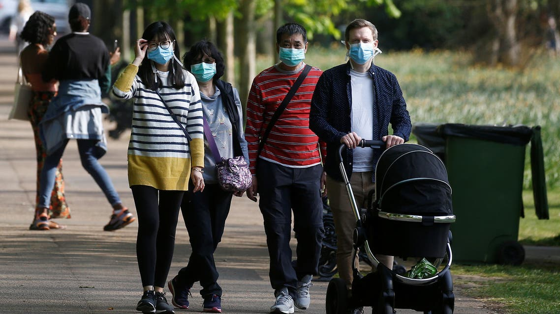 People are seen wearing protective face masks in Greenwich Park as the spread of the coronavirus disease (COVID-19) continues, London, Britain, April 11, 2020. REUTERS/Henry Nicholls