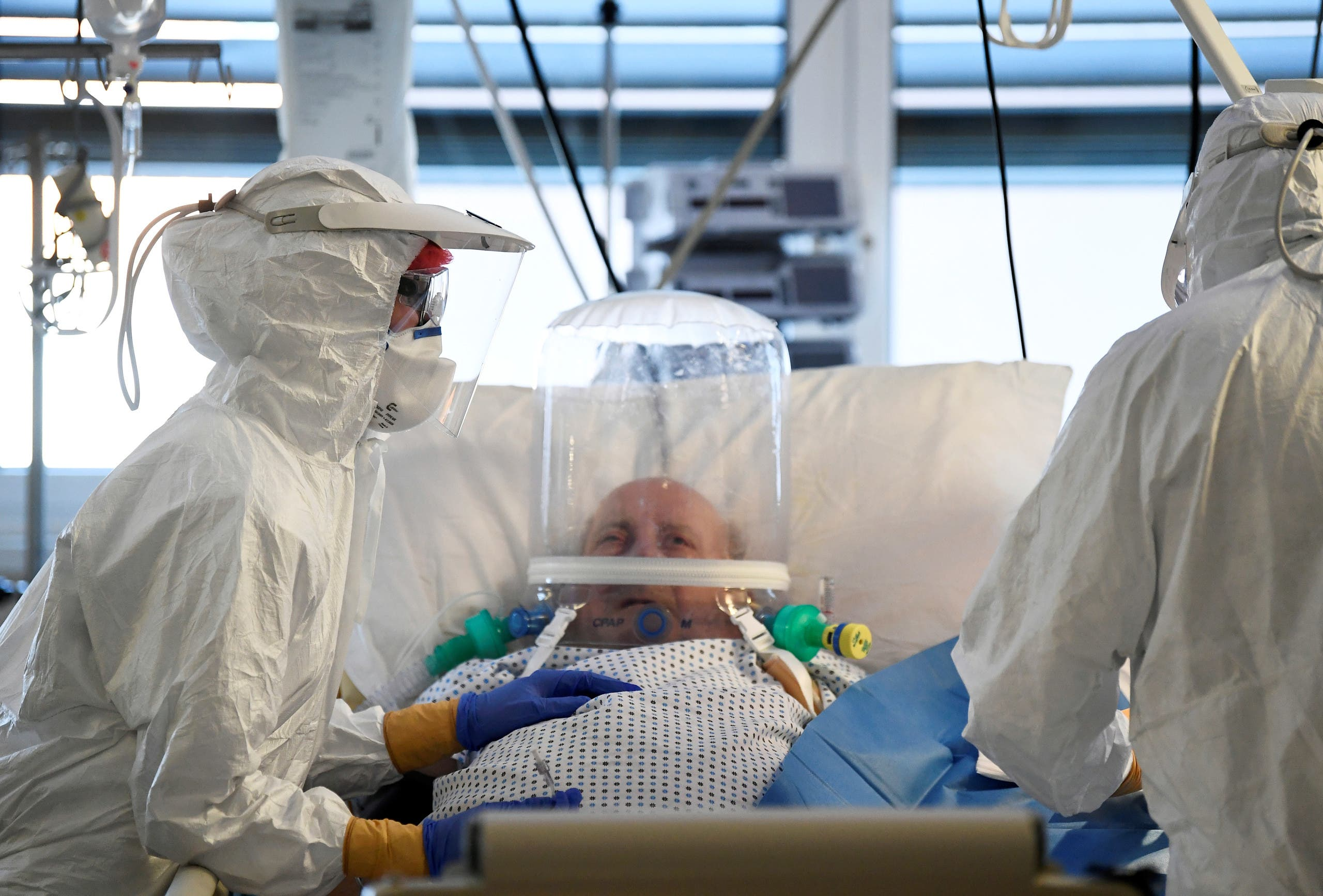 Medical staff members are seen next to a patient suffering from the coronavirus disease in the intensive care unit at the Circolo hospital in Varese, Italy April 9, 2020. (Reuters)