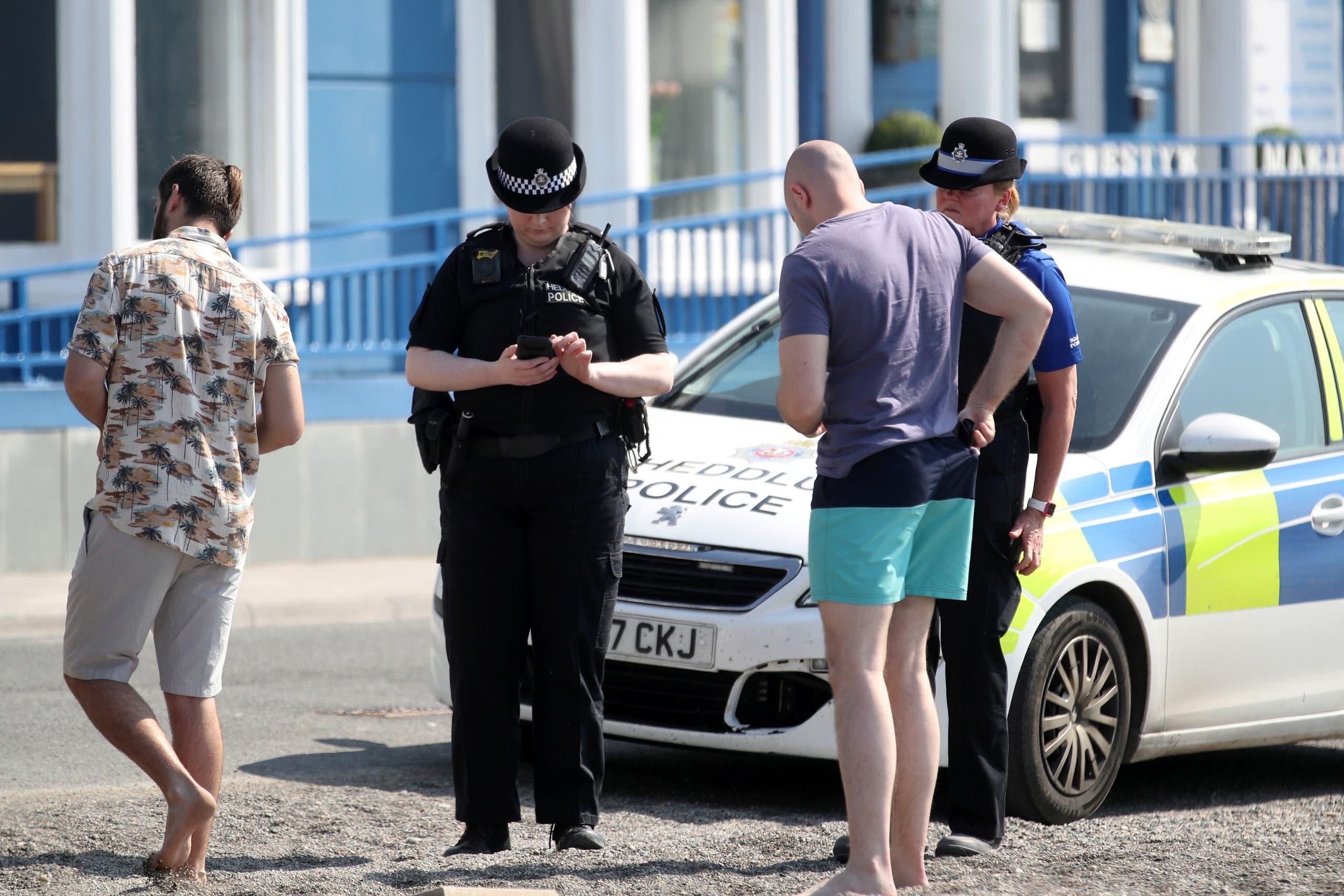 شرطيتان تتحدثان مع رجلين لم يحترما الإغلاق في ويلز بالمملكة المتحدة وكانا يلعبان على الشاطئ