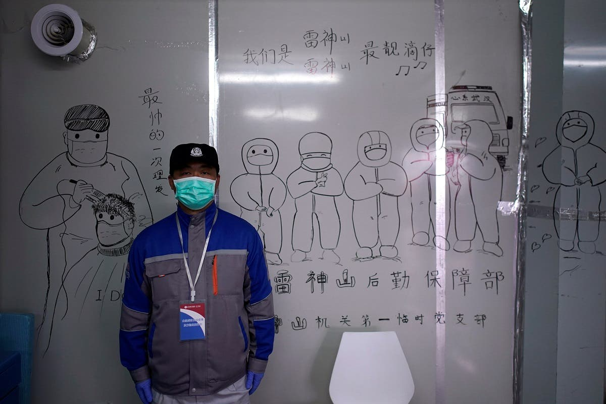 Security guard wearing a face mask stands in front of a sketch depicting medical workers inside the Leishenshan Hospital, a makeshift hospital for treating patients with the coronavirus disease (COVID-19), in Wuhan, Hubei. (Reuters)
