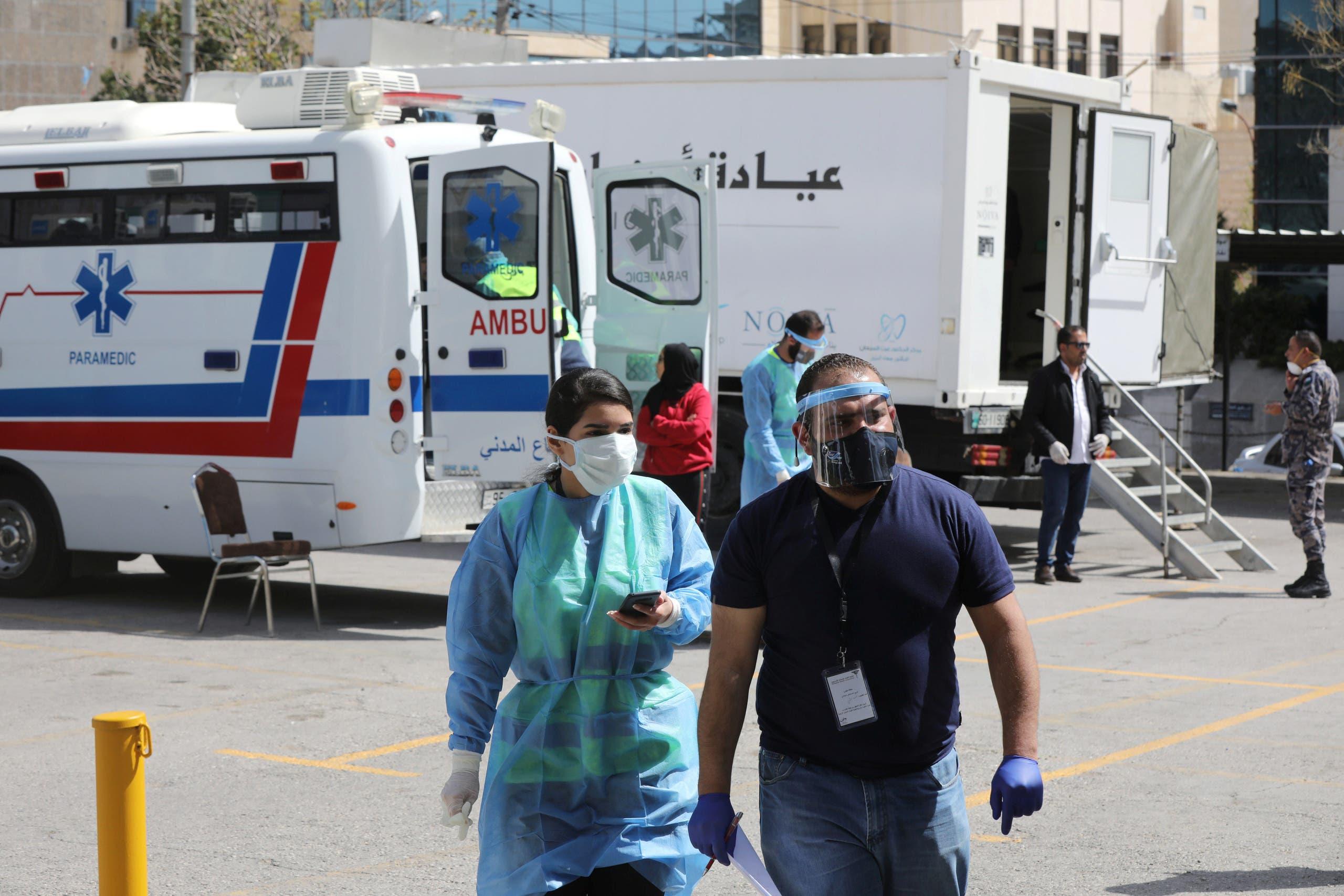 طبيبان أردنيان بالقرب من عيادة متنقلة في عمّان يوم 30 مارس (رويترز)
