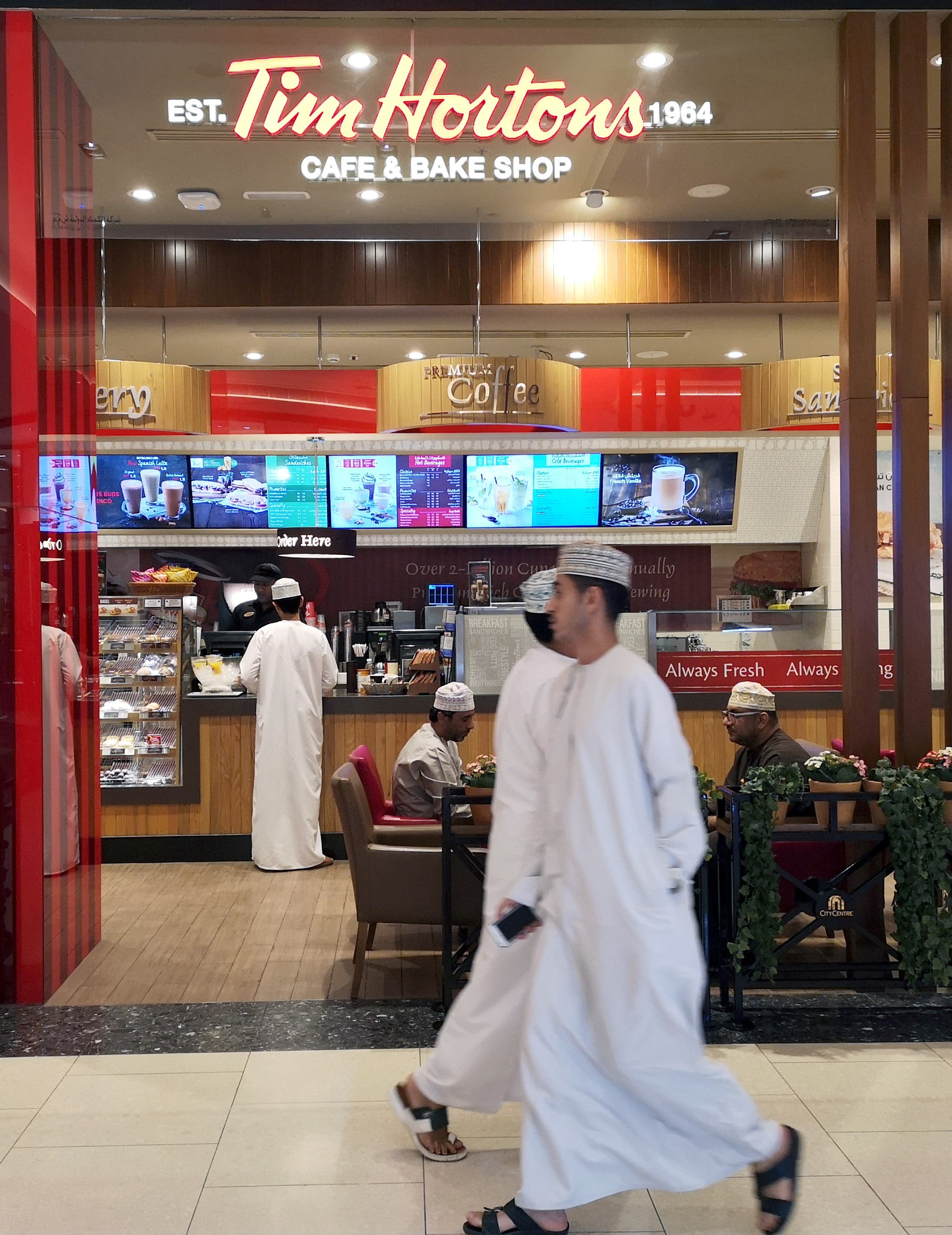 Omani men pass in front of Canadian cafe and bake shop Tim Hortons in City Center Mall in Muscat, Oman. (File photo: Reuters)
