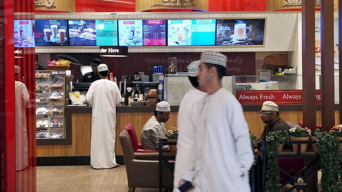Omani men pass in front of Canadian cafe and bake shop Tim Hortons in City Center Mall in Muscat, Oman, February 11, 2019. (Reuters)