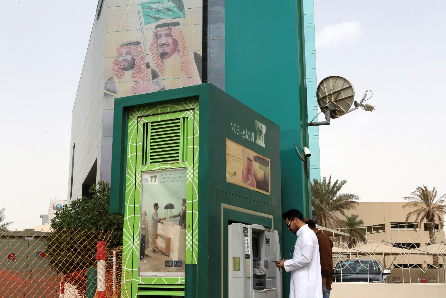 A man withdraws money from an ATM outside the Saudi National Commercial Bank (NCB), after an outbreak of coronavirus, in Riyadh, Saudi Arabia, March 18, 2020. (Reuters)