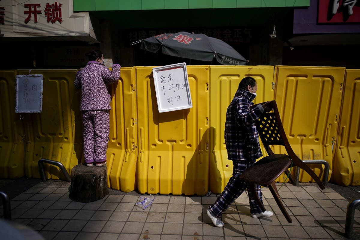 A resident pays for groceries by standing on a tree stump to peer over barriers set up to ring fence a wet market on a street in Wuhan, the epicentre of China's coronavirus disease outbreak, on April 1, 2020. (Reuters)