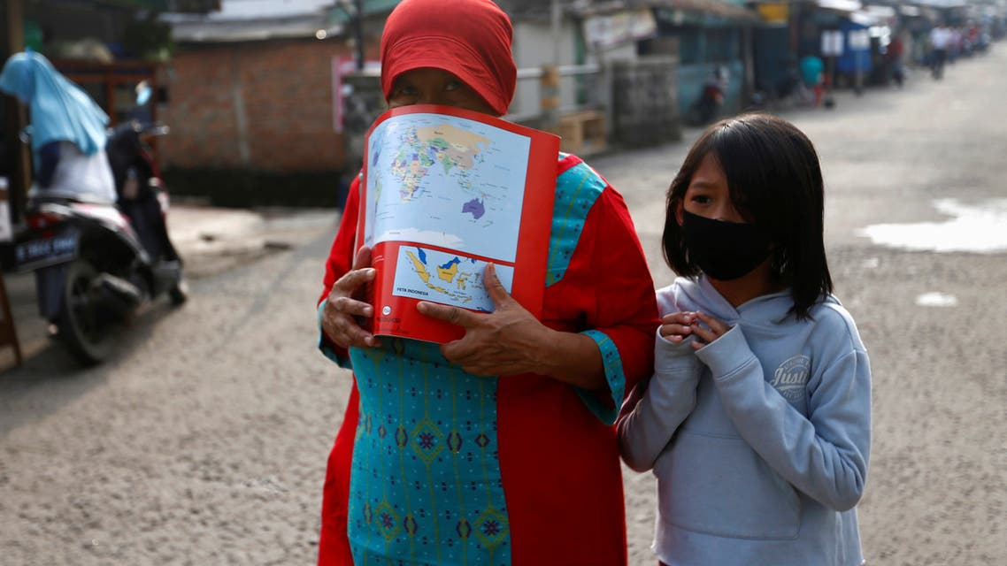 A woman wearing a drawing book as a mask and a girl wearing a protective mask walk amid the coronavirus disease (COVID-19) outbreak, in Depok near Jakarta, Indonesia, April 13, 2020. REUTERS