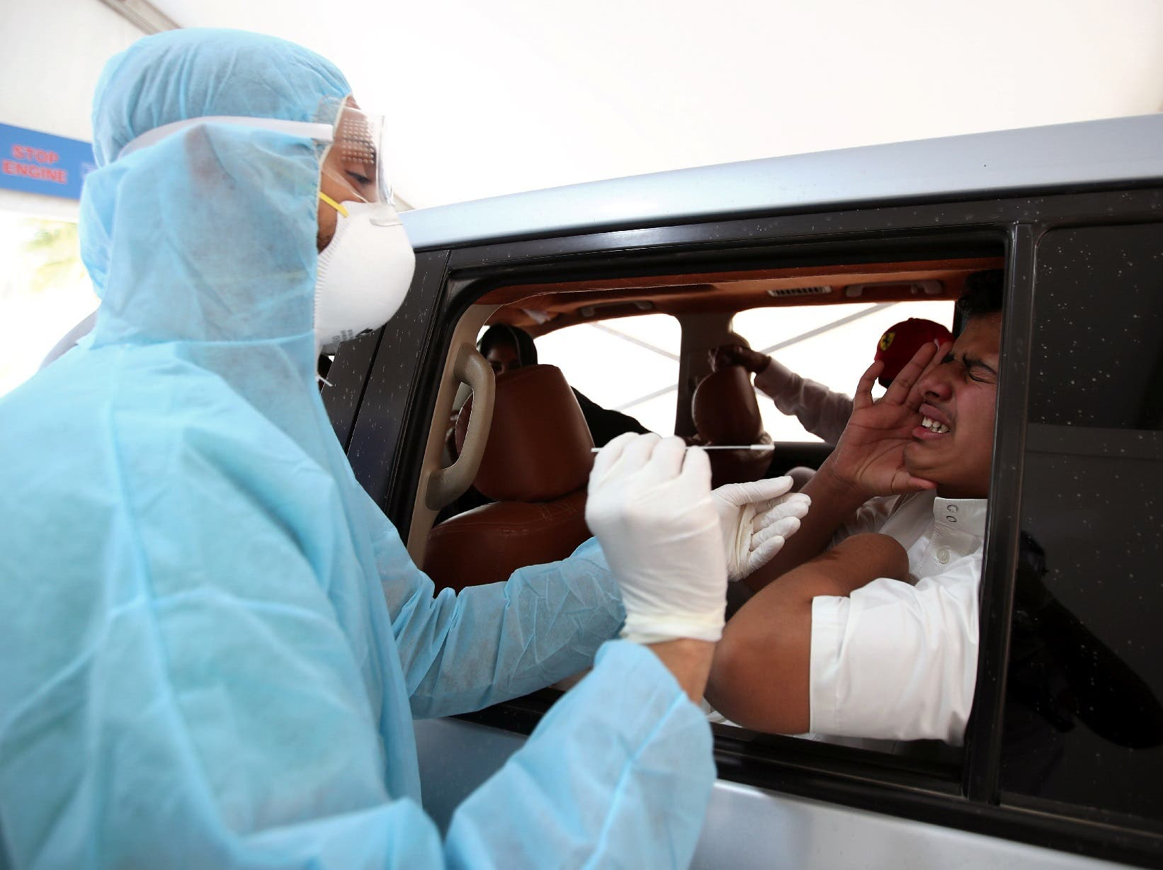 A member of medical staff wearing a protective face mask and gloves takes a swab from a man during drive-thru coronavirus disease (COVID-19) testing at Bahrain Exhibition Center, in Manama, Bahrain April 9, 2020. (Reuters)