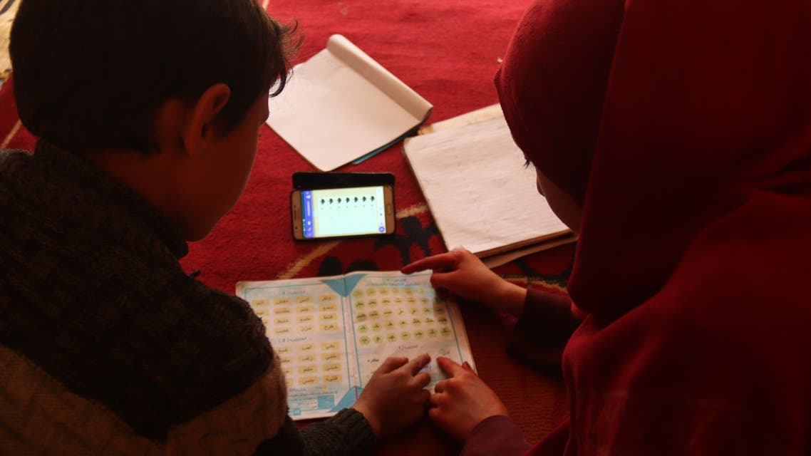 Um Yazan's children study their lessons in the family's tent, sharing a single mobile phone to follow along with the teacher on April 5. (Muhammad Al Hosse)