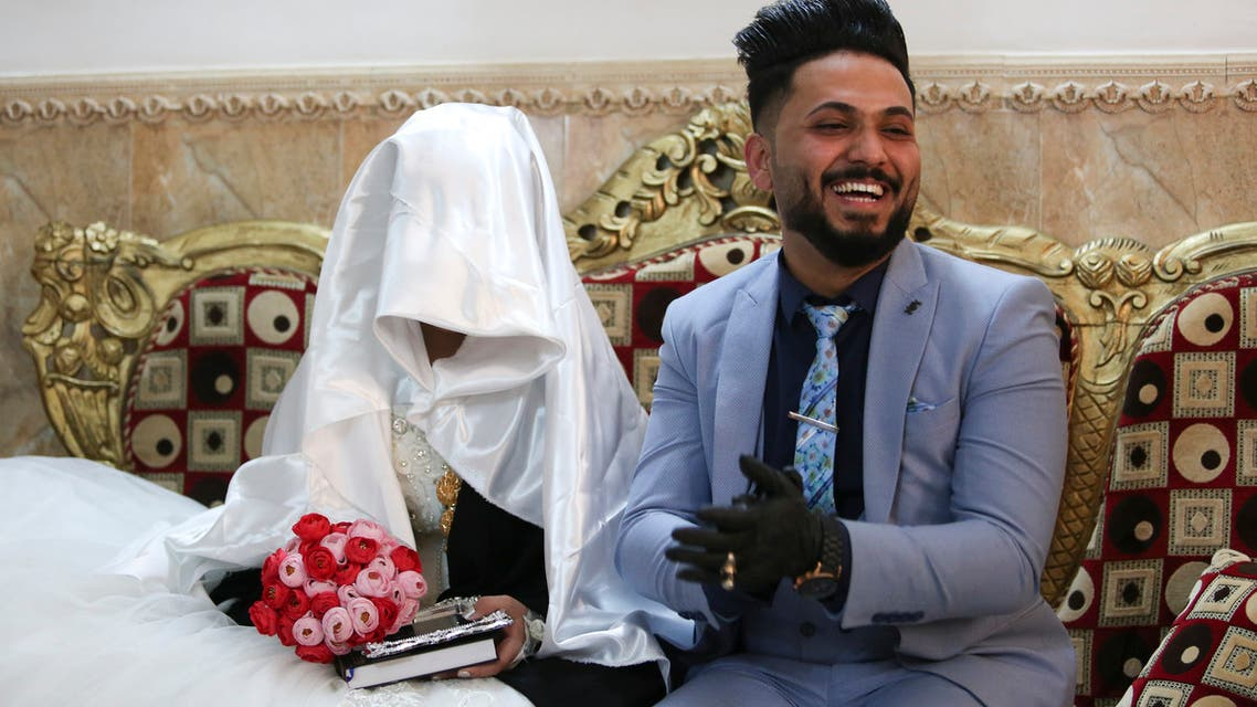 Ahmed Khaled al-Kaabi and his bride Ruqaya Rahim sit during their wedding in Najaf, Iraq, hardest hit town by coronavirus in the country. (AP)