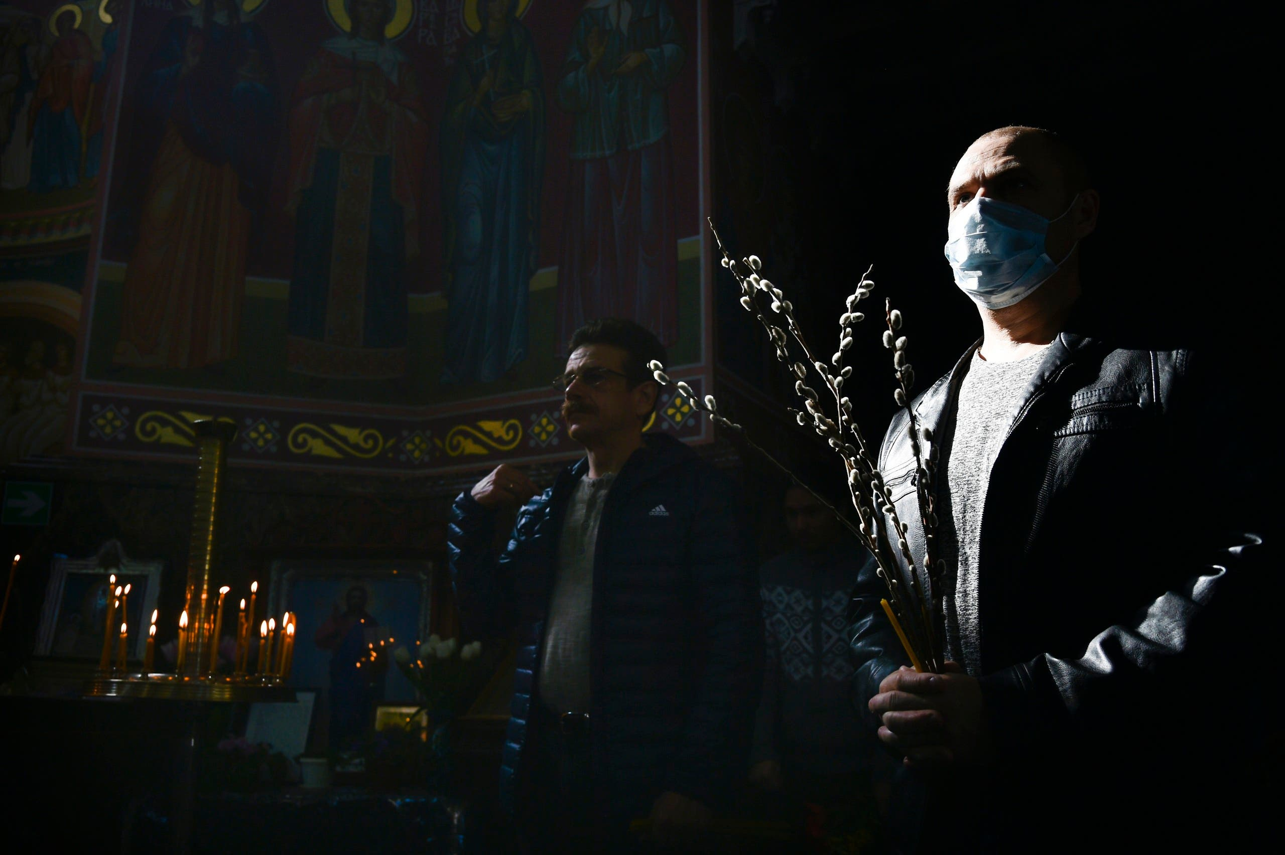 Orthodox Church believers, some wearing face masks to protect from coronavirus, attend a religion service inside a church celebrating Orthodox Palm Sunday in Yevpatoria, Crimea, on April 12, 2020. (AP)