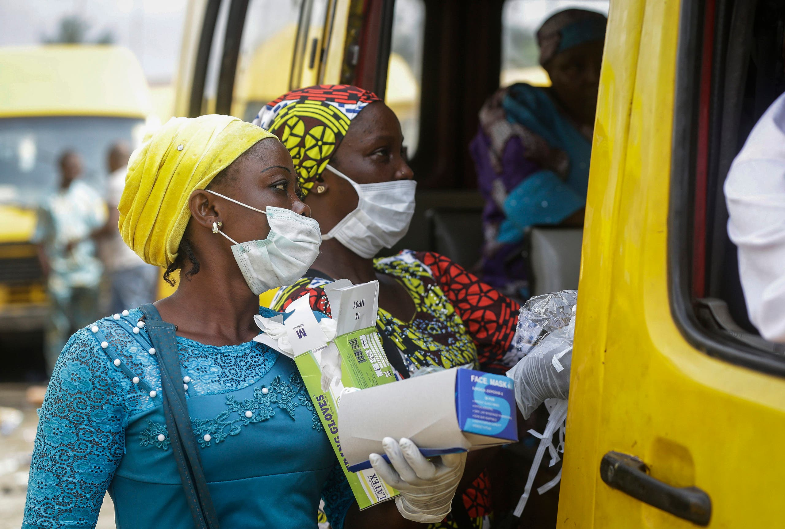 Women sell face masks and gloves, to prevent the spread of the new coronavirus, to passengers at a public minibus station in Lagos, Nigeria on Friday, March 27, 2020. (AP)
