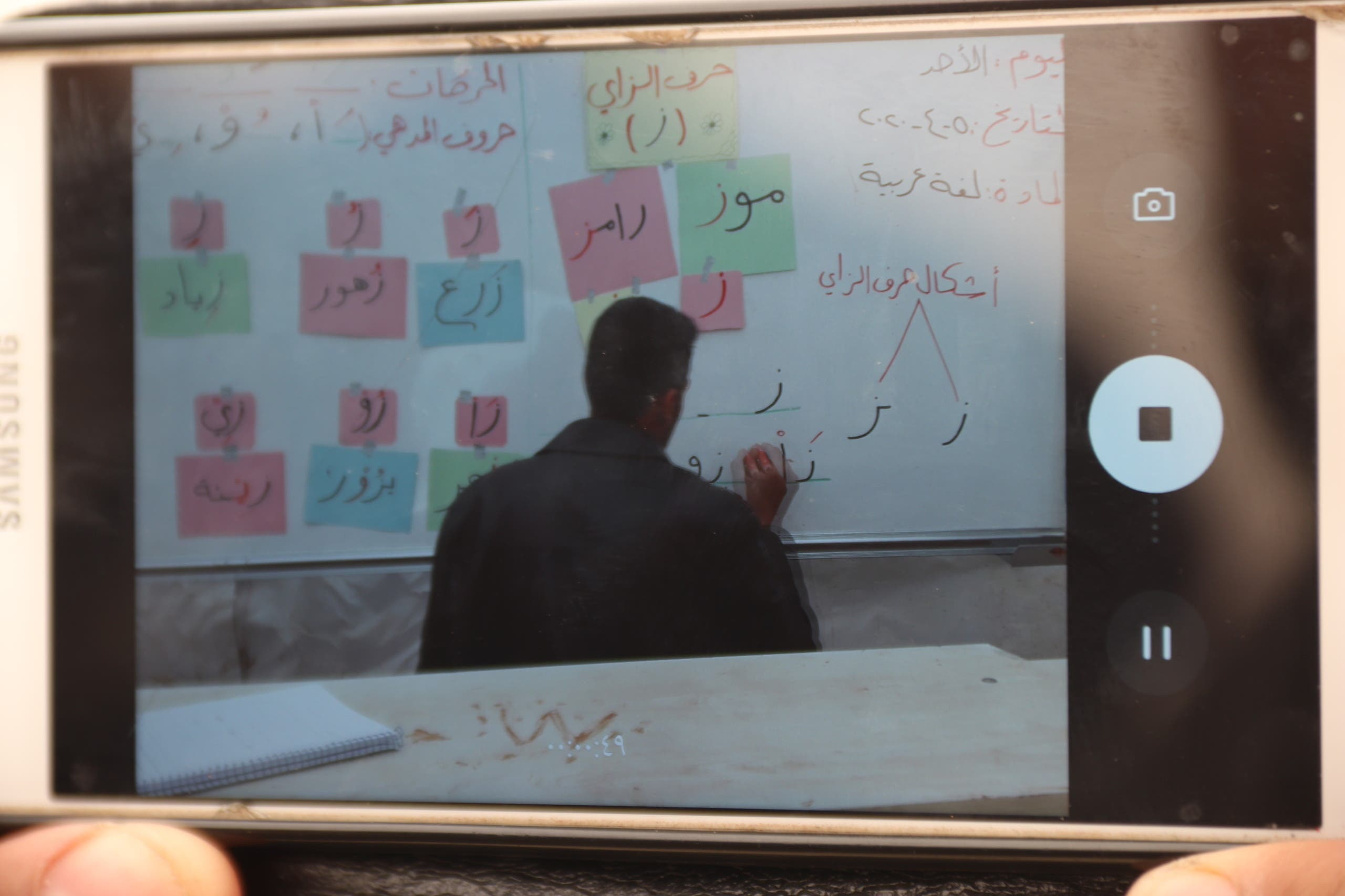 Teachers film and stream an Arabic language lesson in Kahatein camp in Harbanoush, Syria. (Muhammad Al Hosse)