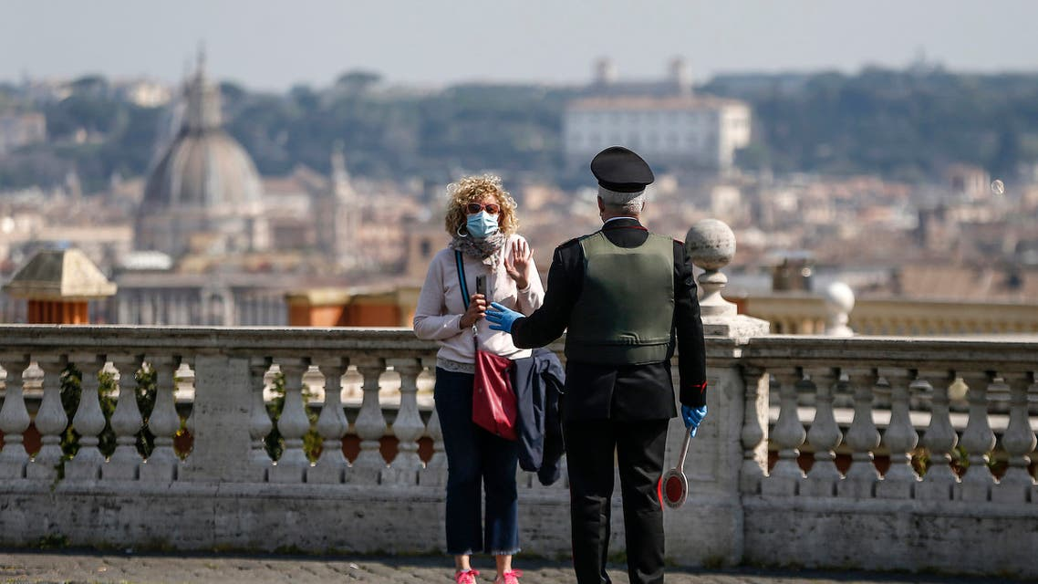 A carabineri police officer talks to a woman wearing a face mask at the Gianicolo hill overlooking Rome, on April 13, 2020. (File photo: AP)
