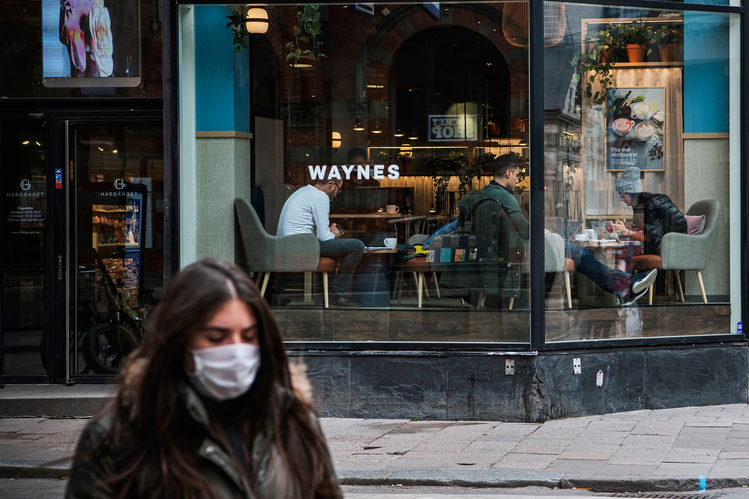 شابة ترتدي كمامة خلال مرورها أمام مقهى مزدحم في ستوكهولم