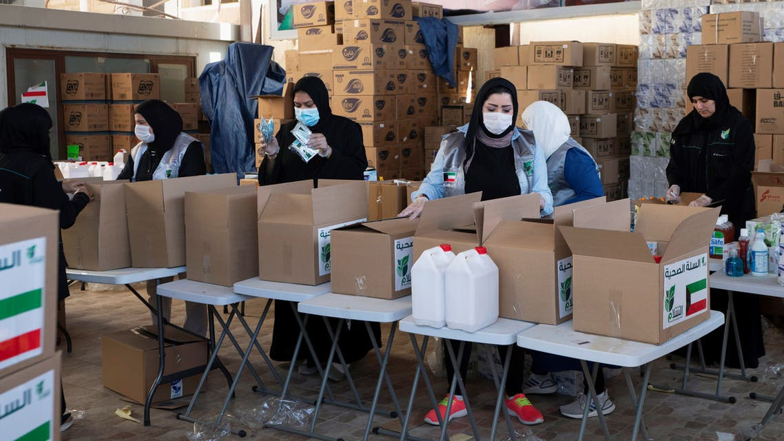 Kuwaiti volunteers wear protective masks as they fill charity boxes with essential household supplies to distribute to the needy, following the outbreak of the coronavirus disease (COVID-19), in Adeliah, Kuwait April 4, 2020. Picture taken April 4, 2020. REUTERS/Stephanie McGehee