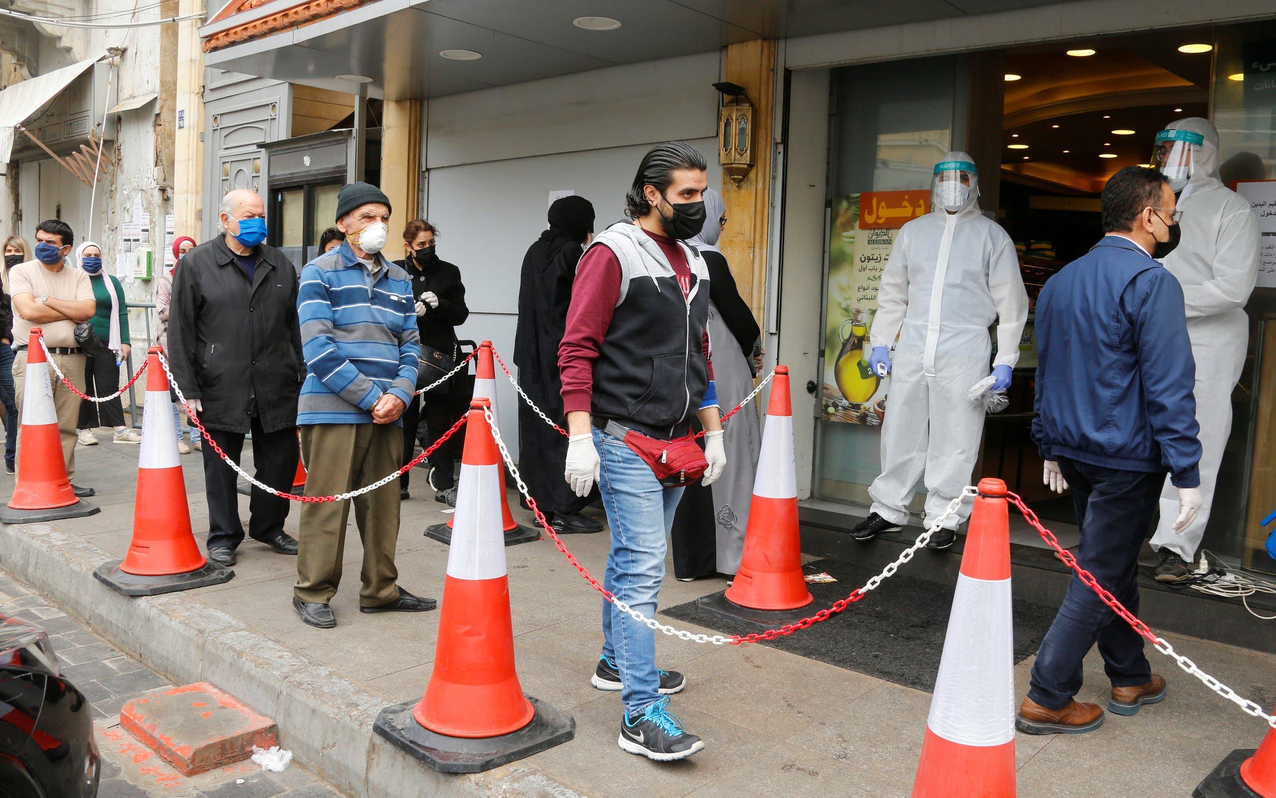 زبائن يرتدون الكمامات والقفازات وينتظرون دورهم للدخول إلى سوبرماركت في بيروت
