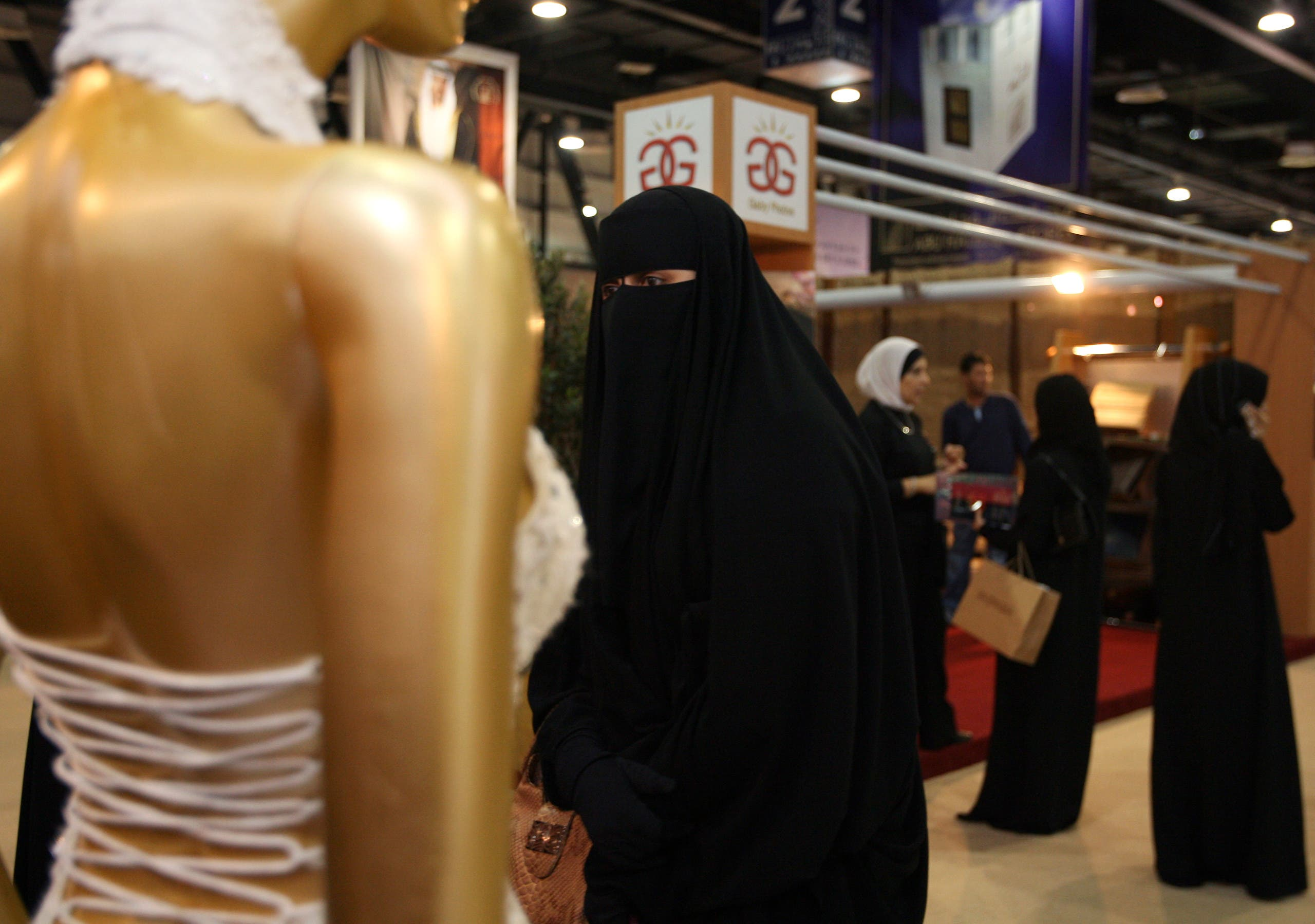 A woman walks past a wedding dress on display at The Bride Show in Dubai, United Arab Emirates. The event, for the wedding industry, is held for four days in Dubai. (File photo: Reuters)