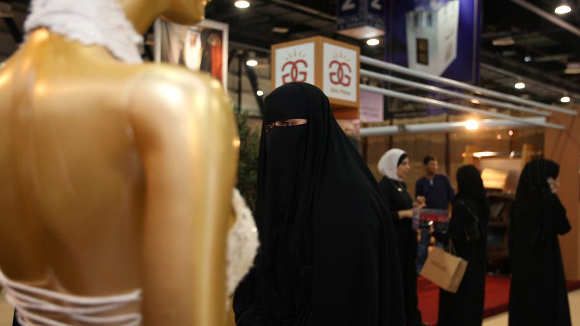 A woman walks past a wedding dress on display at The Bride Show in Dubai, United Arab Emirates. The event, for the wedding industry, is held for four days in Dubai. (Reuters)