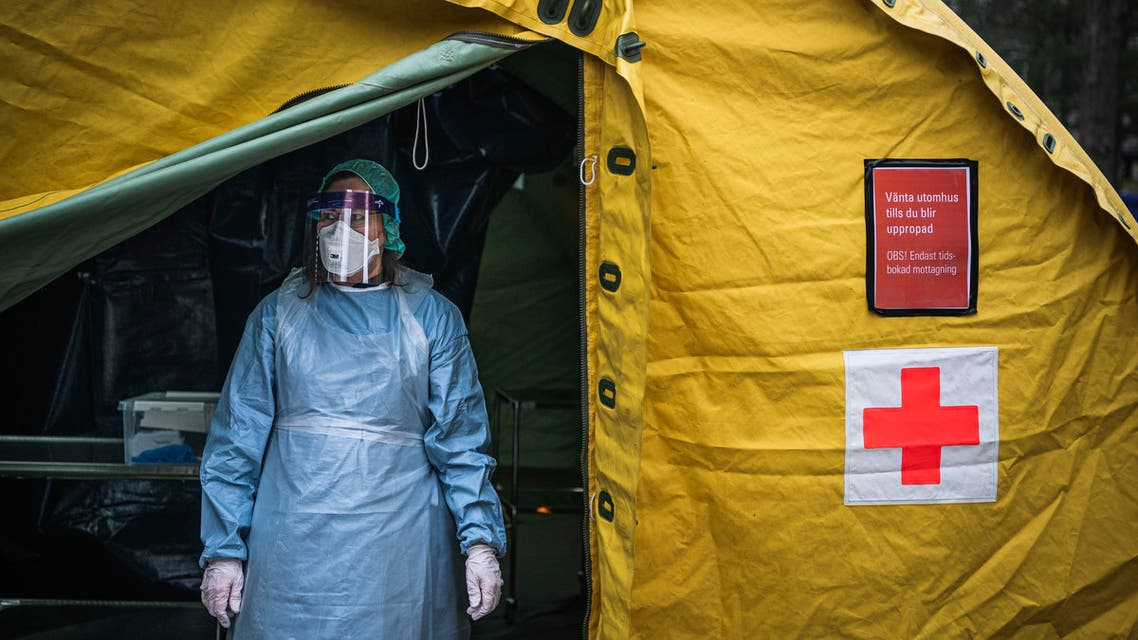 A medical staffer at Sophiahemmet hospital stands at the entrance of a tent for testing and receiving potential coronavirus COVID-19 patients on April 7, 2020 in Stockholm.