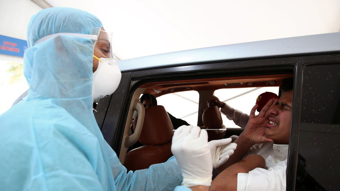 A member of medical staff wearing a protective face mask and gloves takes a swab from a man during drive-thru coronavirus disease (COVID-19) testing at Bahrain Exhibition Center, in Manama, Bahrain April 9, 2020. REUTERS/Hamad I Mohammed