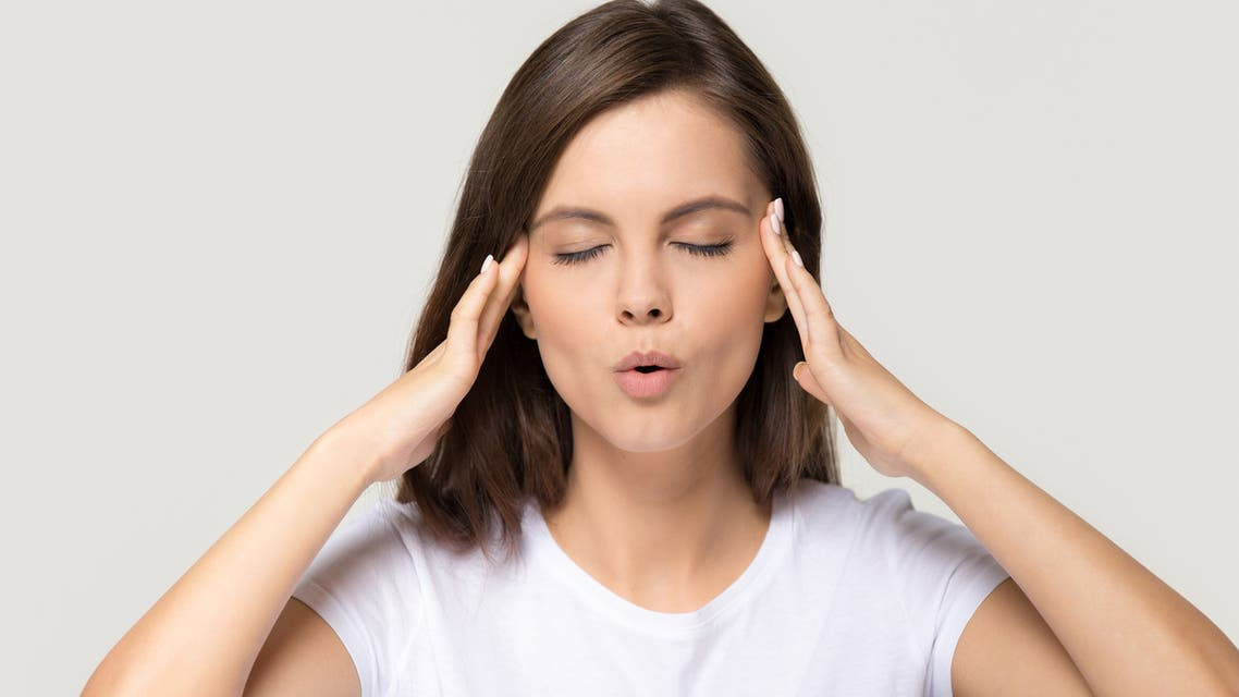 Stressed teen girl calming down massaging temples isolated on background stock photo