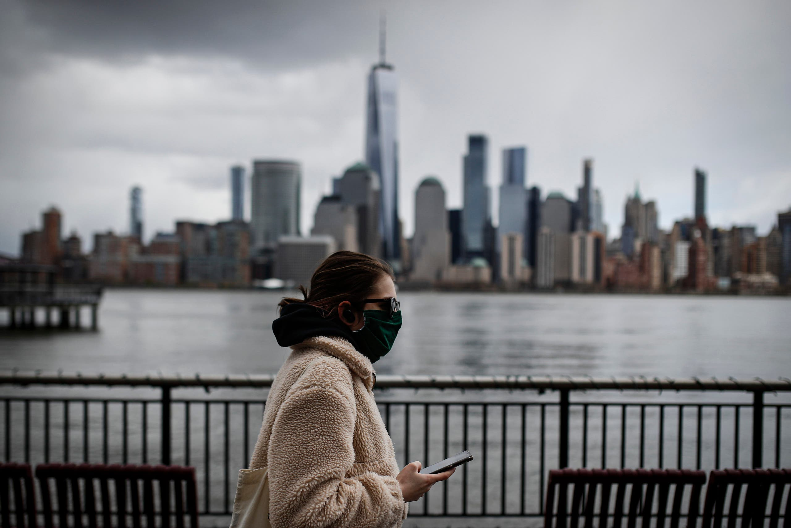 The downtown New York City skyline looms over pedestrians wearing masks due to COVID-19 concerns, Friday, April 10, 2020, in Jersey City, N.J. (AP)