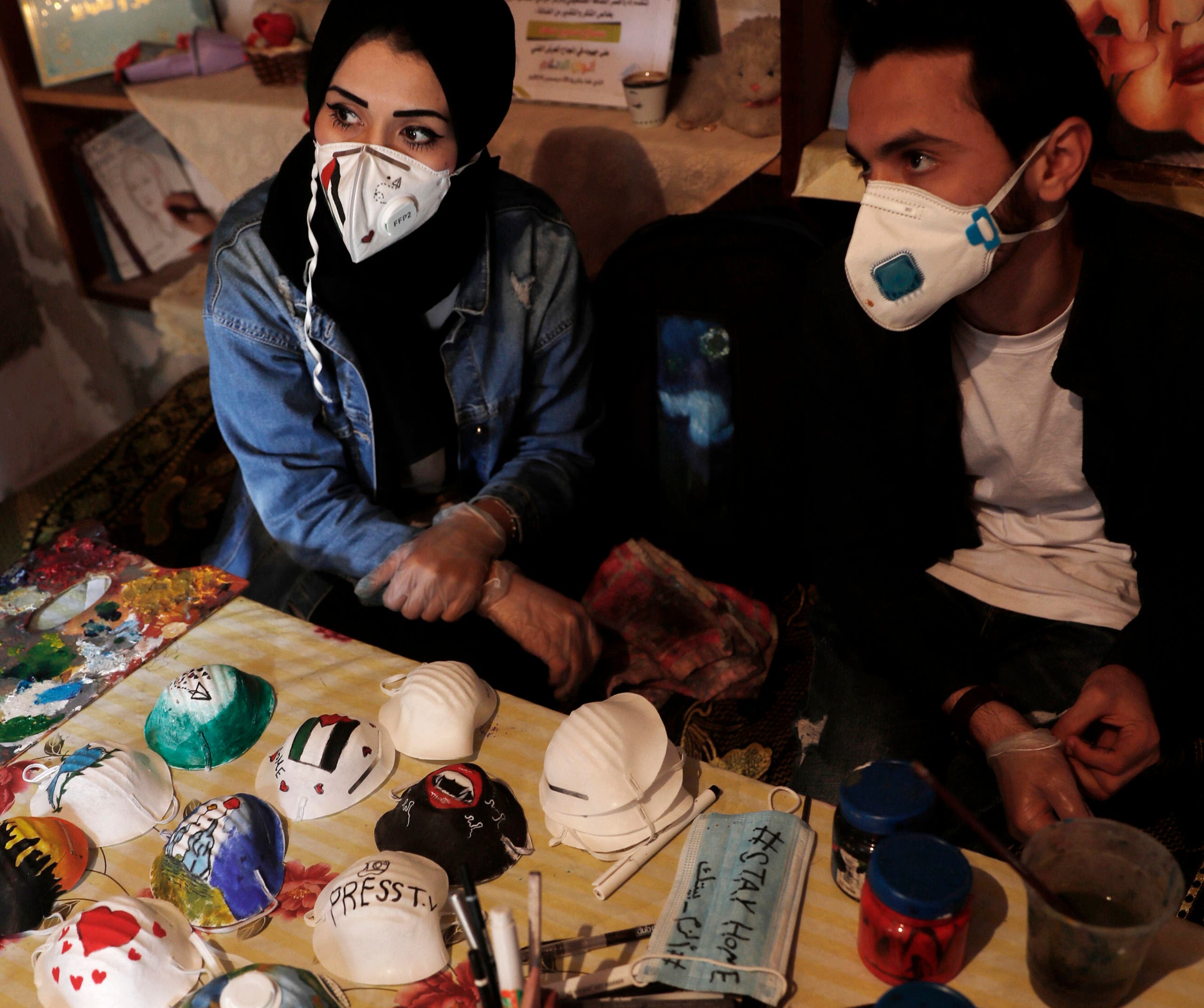 Palestinian artists Dorgham Qeraqea, left, and Samah Saed decorate protective face masks to encourage people to wear them as a precaution against the coronavirus, at a workshop in the Shijaiyah neighborhood of Gaza, Thursday, April 2, 2020. (AP)