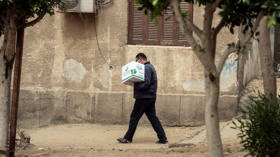 An Egyptian man carries a box with foodstuffs outside a centre of non-governmental organisation Egyptian Food Bank on April 05, 2020. (AFP)
