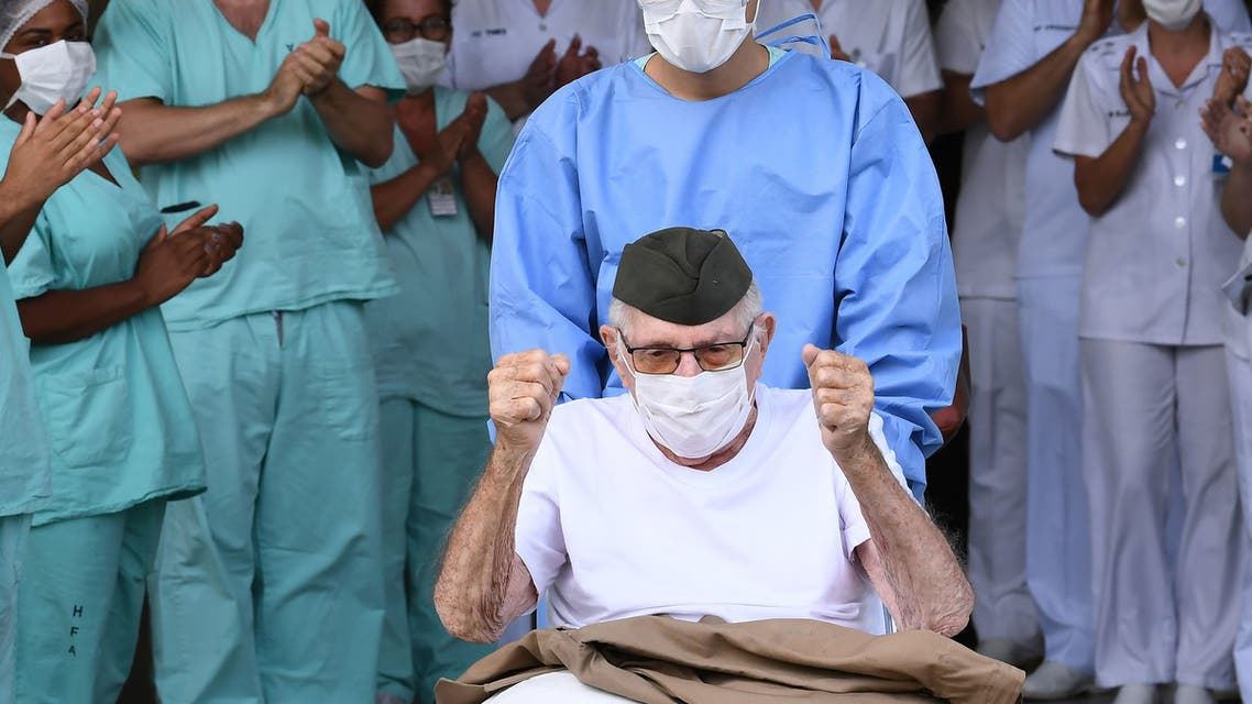 """Brazilian 99-year-old former WWII combatant Ermando Armelino Piveta, leaves the Armed Forces Hospital in Brasilia, after being treated for the novel coronavirus COVID-19 and discharged, on April 14, 2020. Piveta was admitted to hospital on April 6 and treated at the hospital's """"COVID Ward"""", reserved for positive cases of the disease."""
