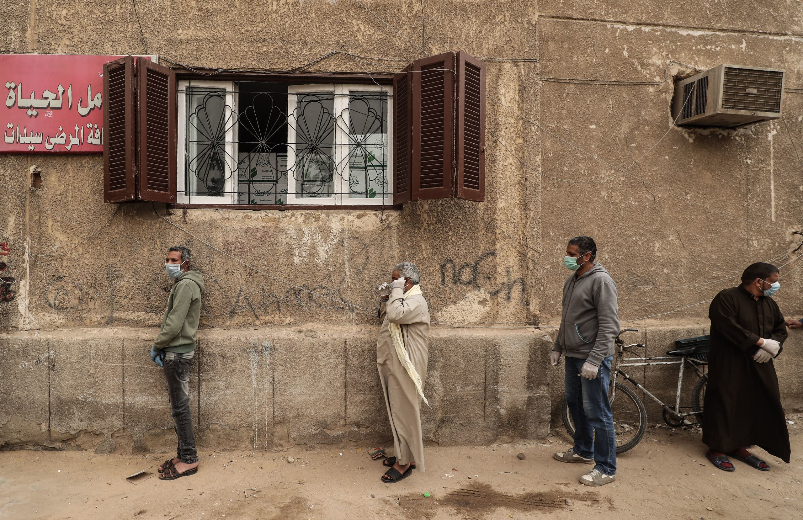 Egyptian men wearing masks wait outside a center of non-governmental organisation Egyptian Food Bank to receive cartons with foodstuffs. (File photo: AFP)