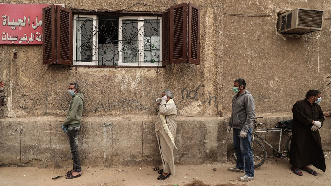 Egyptian men wearing masks wait outside a centre of non-governmental organisation Egyptian Food Bank to receive cartons with foodstuffs on April 05, 2020. (AFP)