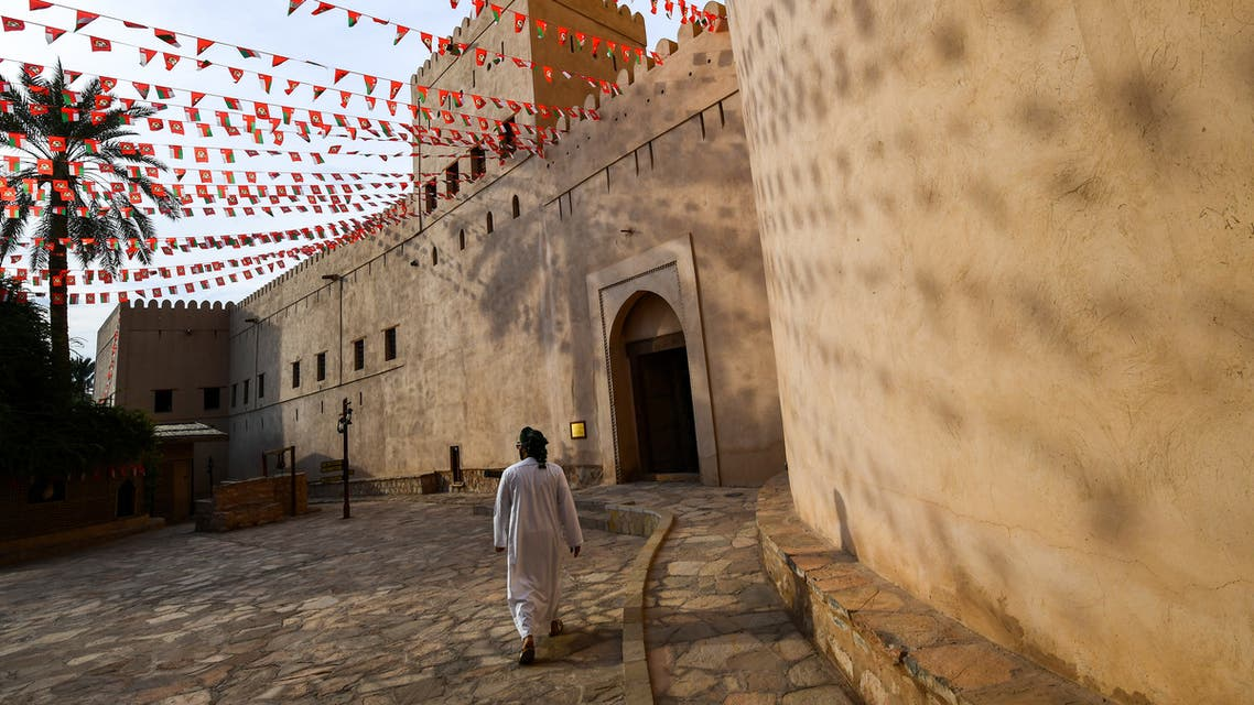 a man walking past the walls of the Nizwa Fort in Oman. (AFP)