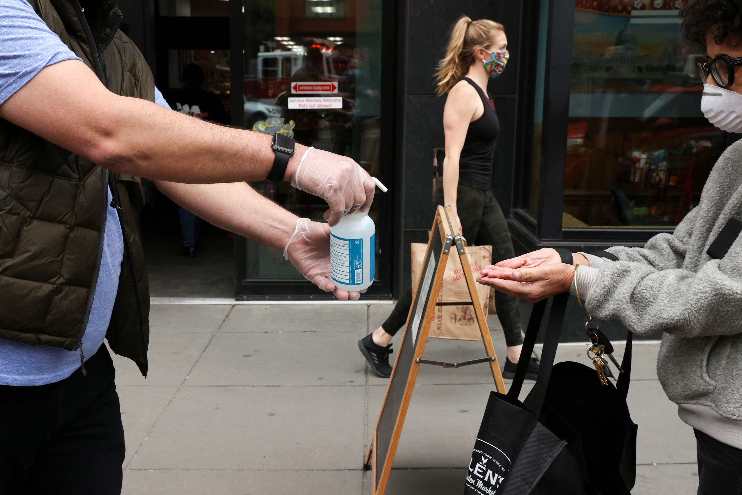 A store worker offers hand sanitizer to shoppers, during the coronavirus disease (COVID-19) outbreak, as they wait in line on the sidewalk outside a grocery store in Washington, U.S., April 14, 2020. (Reuters)