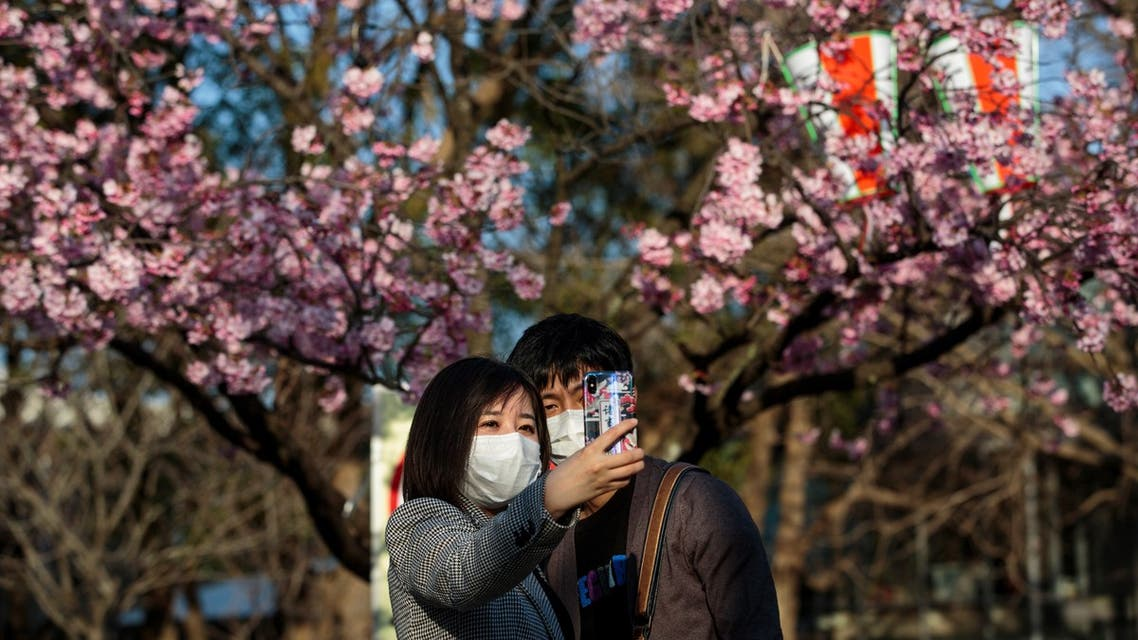 A couple take a selfie with cherry blossoms at Ueno park in the Japanese capital Tokyo. (AFP)