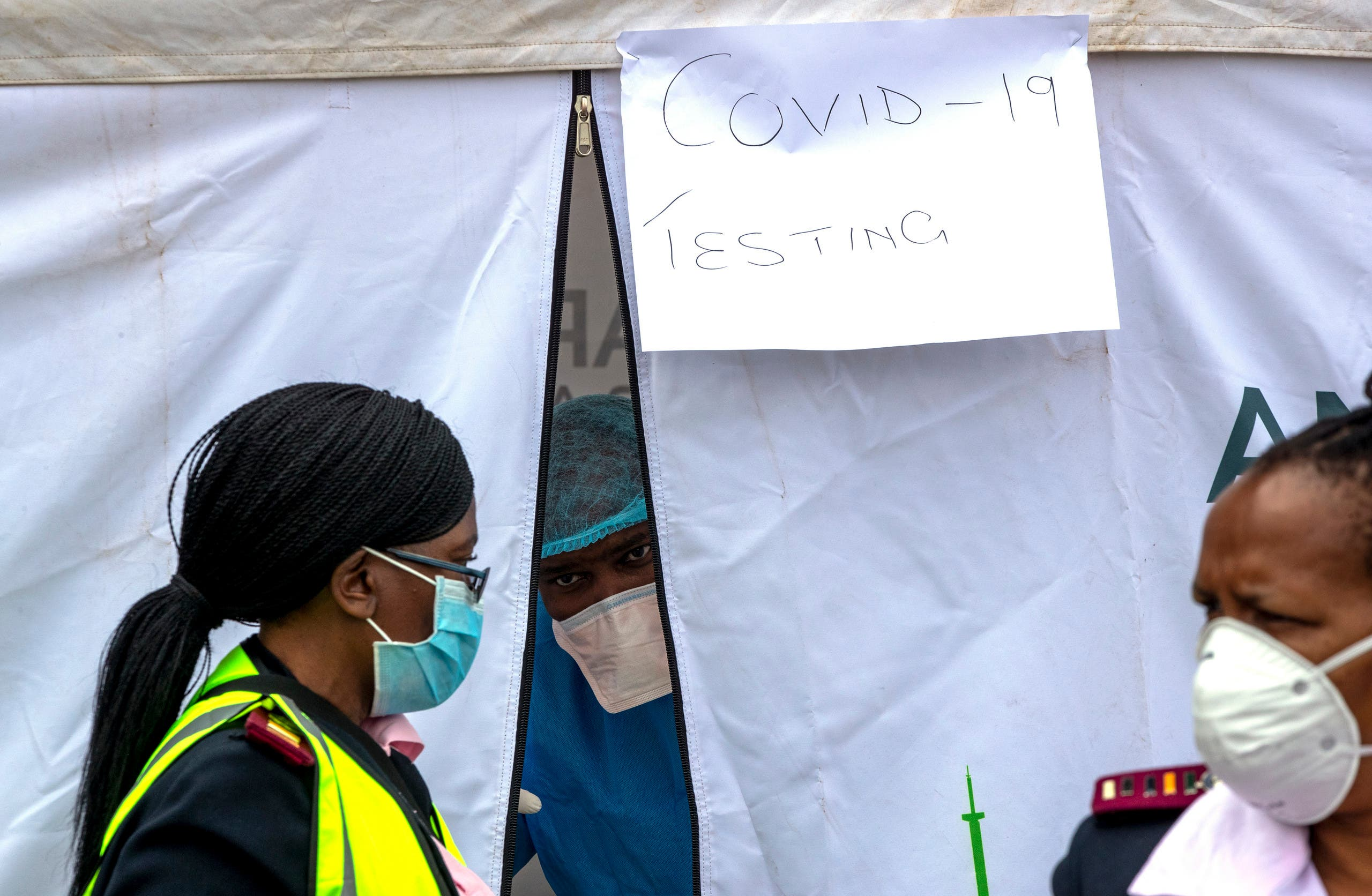 A health worker wearing personal protective gear inside a testing tent, gestures colleagues during the screening and testing for COVID-19, in Lenasia, south of Johannesburg, South Africa on April 8, 2020. (AP)