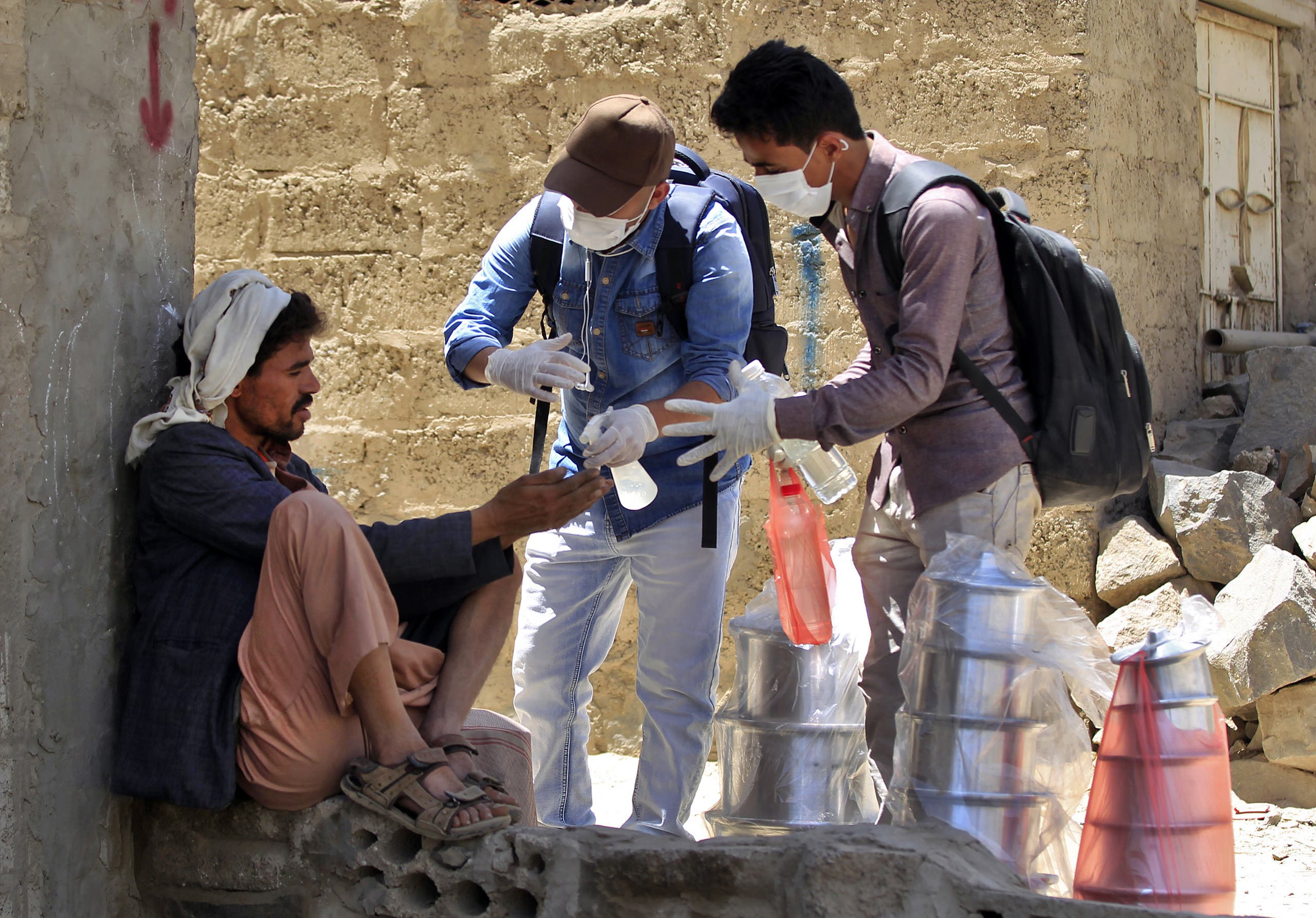 Yemeni volunteers spray disinfectant on the hands of a man in one of Sanaa's impoverished neighborhoods, on March 30, 2020. (AFP)