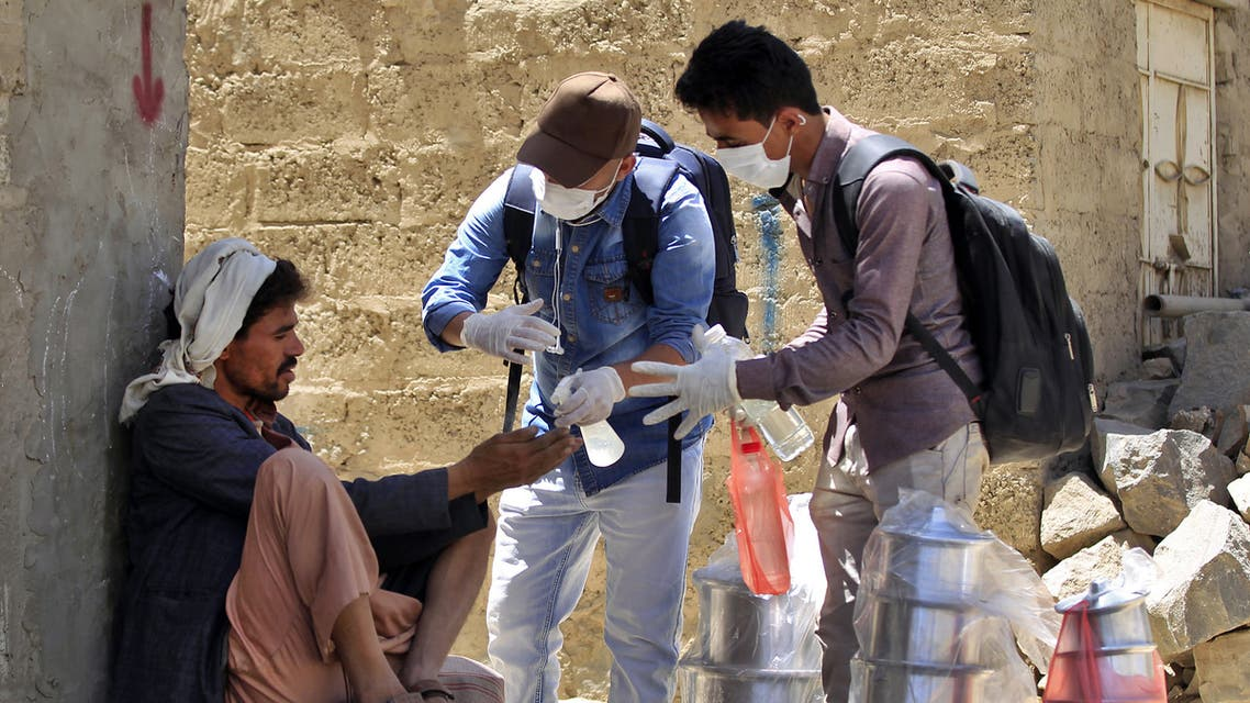 Yemeni volunteers spray disinfectant on the hands of a man in the one of Sanaa's impoverished neighbourhoods, on March 30, 2020, amid concerns of a coronavirus outbreak. (AFP)
