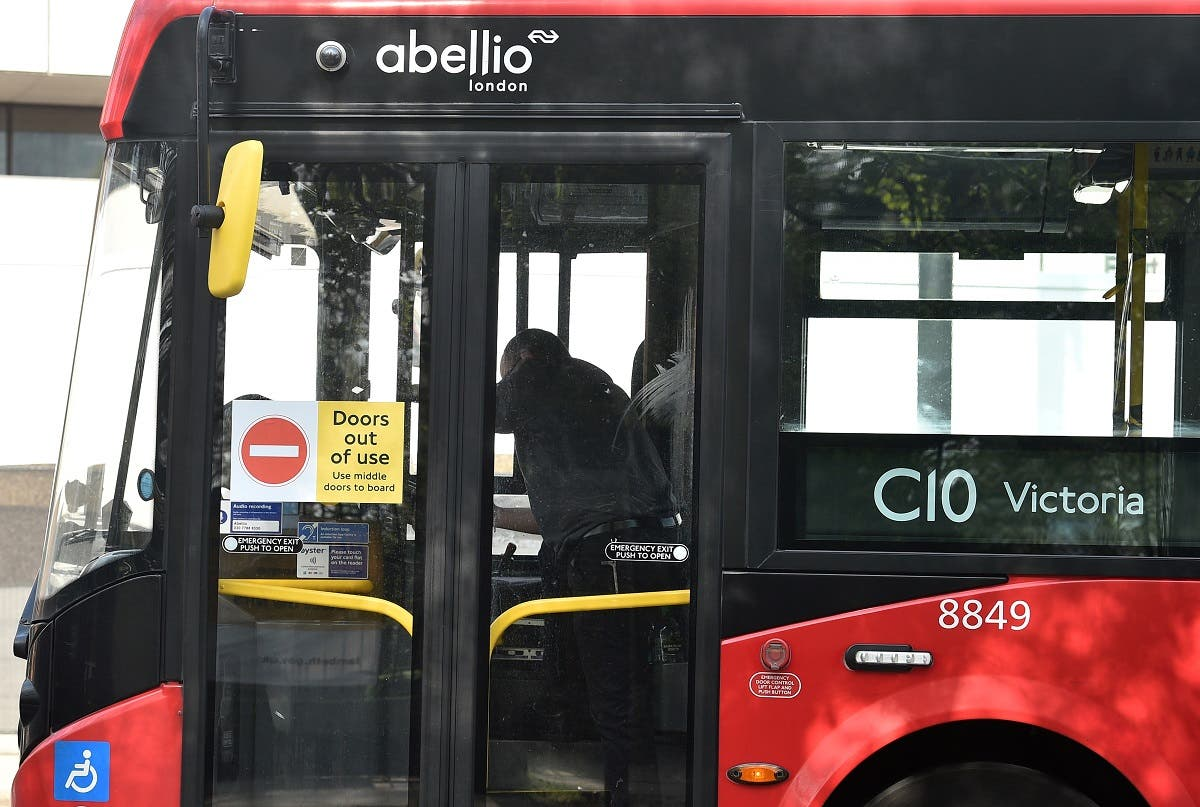 """A sign reading """"Doors out of use"""" is pictured on the front doors of a Transport for London (TfL) bus operated by Abellio, as customers are made to use the middle doors in an effort to keep the driver safe. (AFP)"""