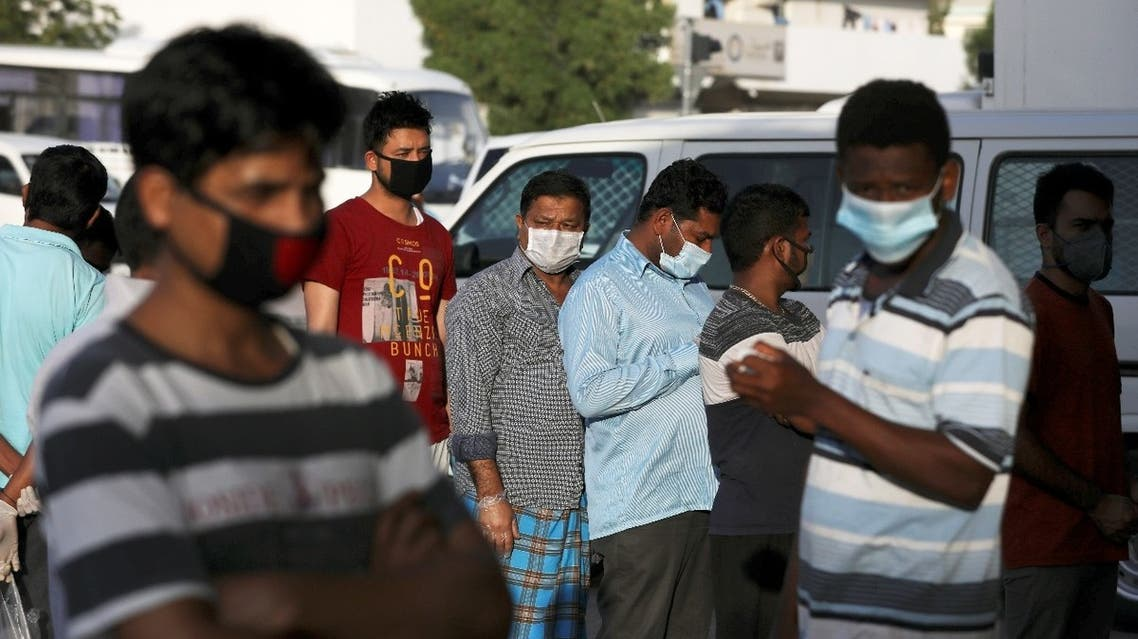 Foreign workers wearing protective face masks queue outside a corner store, following the outbreak of the coronavirus disease (COVID-19), in the Al Quoz industrial district of Dubai, United Arab Emirates, April 14, 2020.  (Reuters)